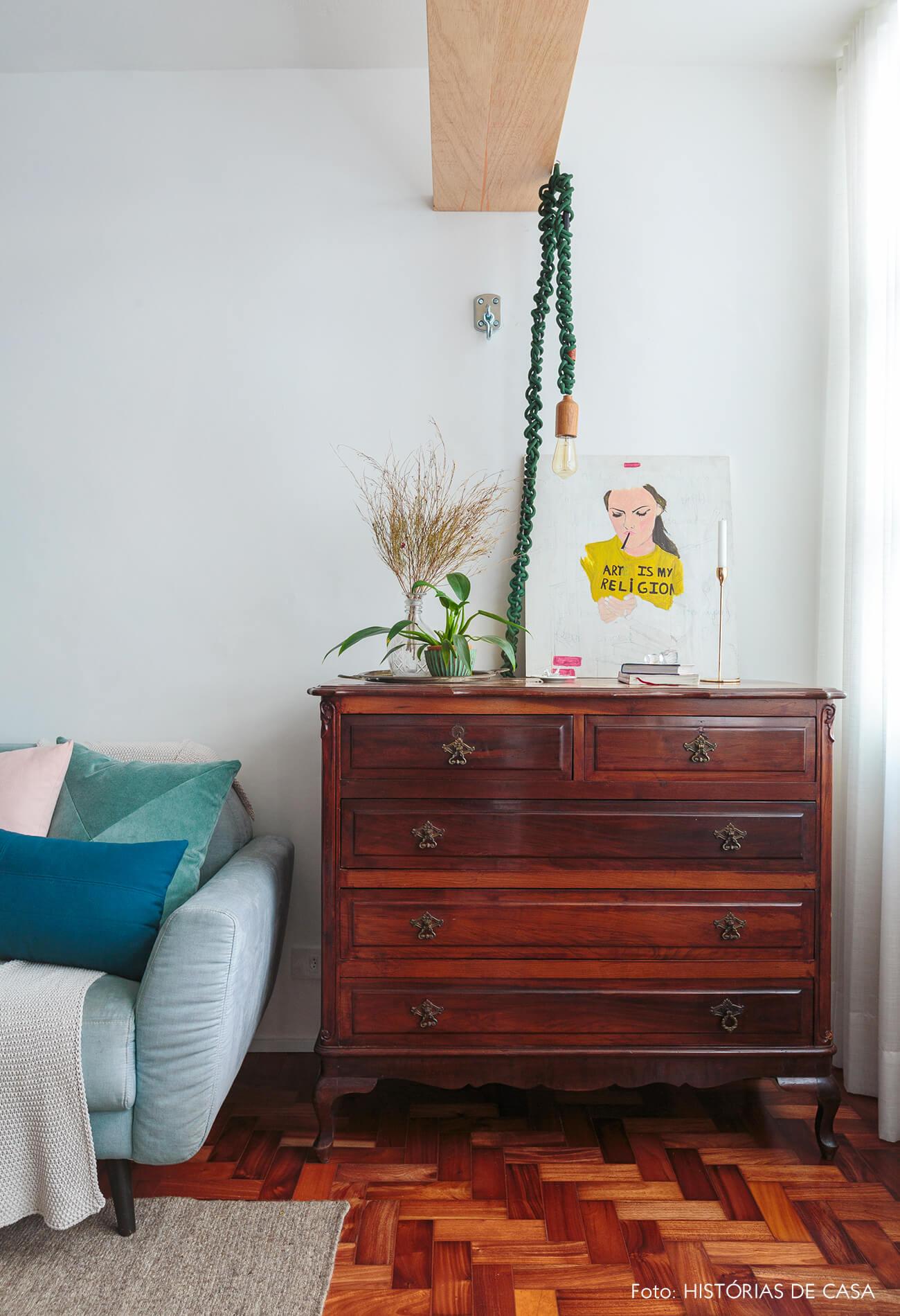 sala-sofa-azul-piso-taco-madeira-tapete-cinza-estante-madeira-escura-luminaria-pendente-verde-almofadas-coloridas
