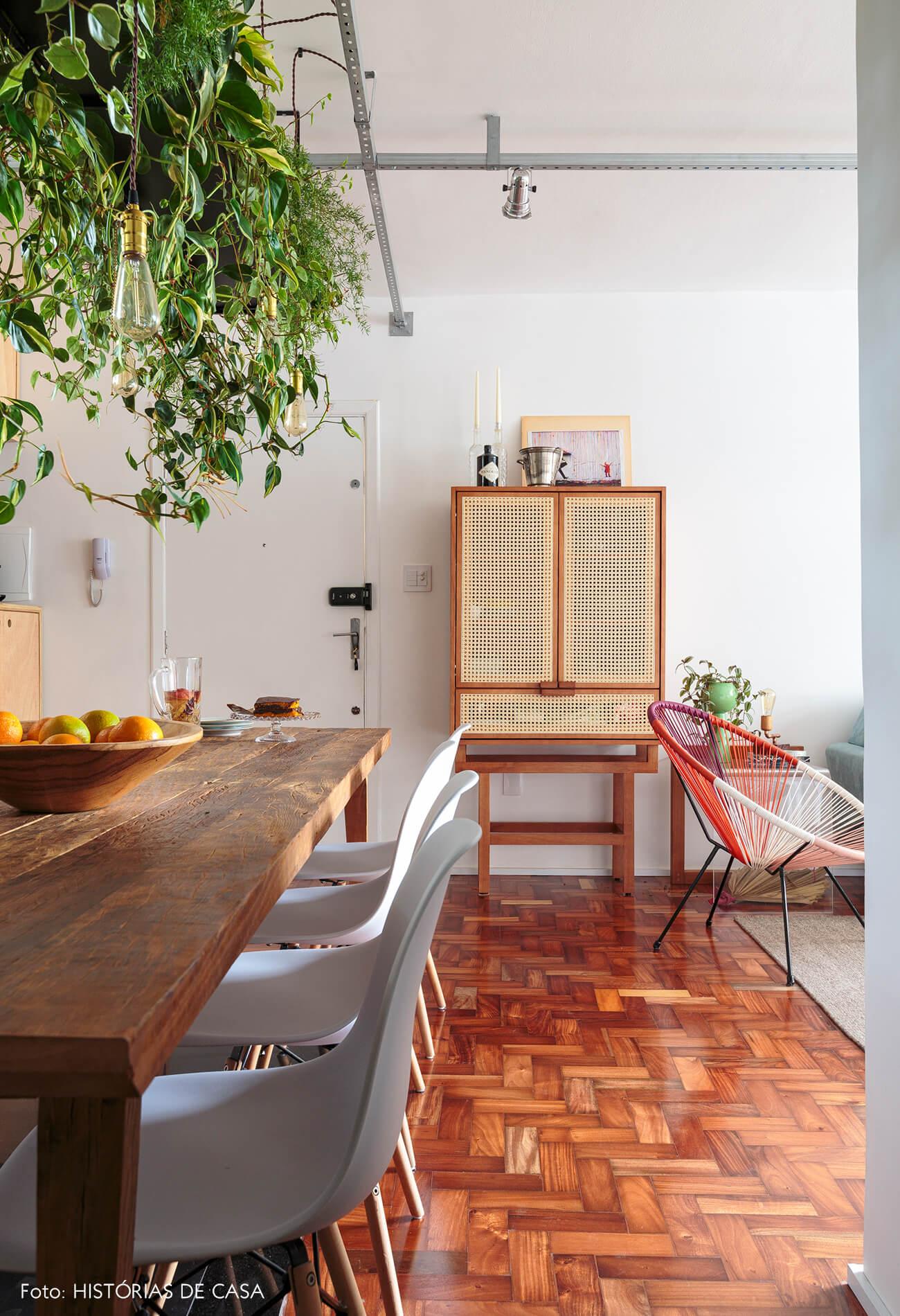 mesa-madeira-escura-piso-taco-madeira-armario-palhinha-plantas-suspensas-cadeira-eames-branca-cadeira-acapulso-rosa-roxa-branca