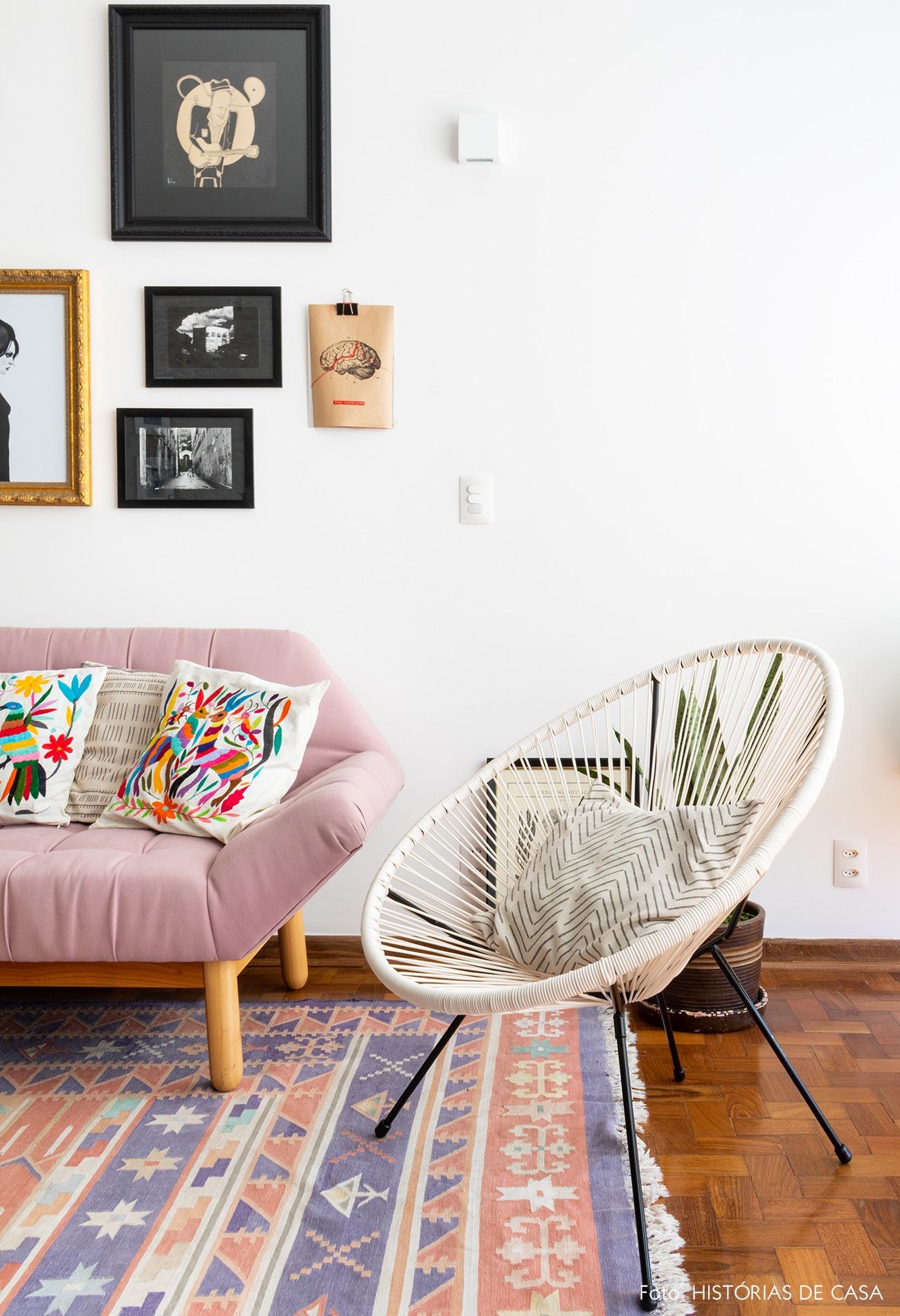 sala-sofa-rosa-cadeira-branca-tapete-estampado-piso-madeira-quadros