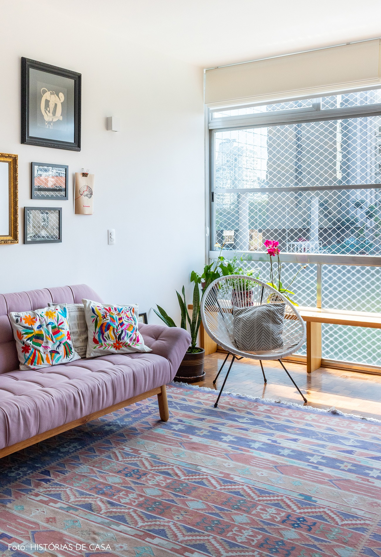 sala-sofa-rosa-tapete-estampado-almofadas-estampadas-cadeira-branca-quadros