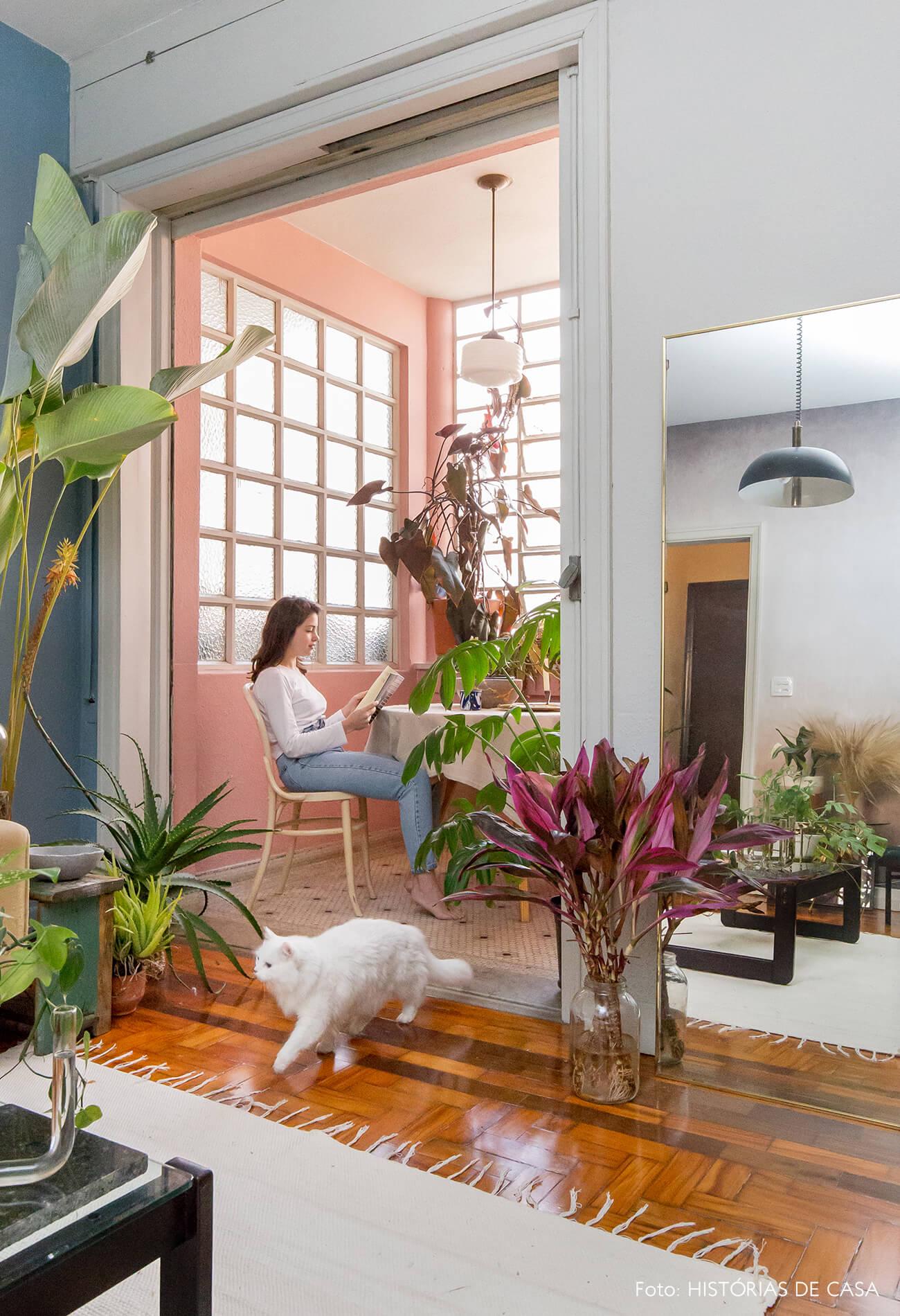 sala com parede rosa e piso de madeira e tapete branco retrato
