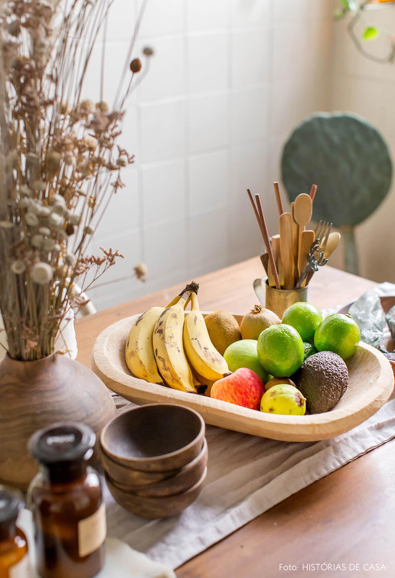 detalhe frutas em prato de madeira em mesa de madeira