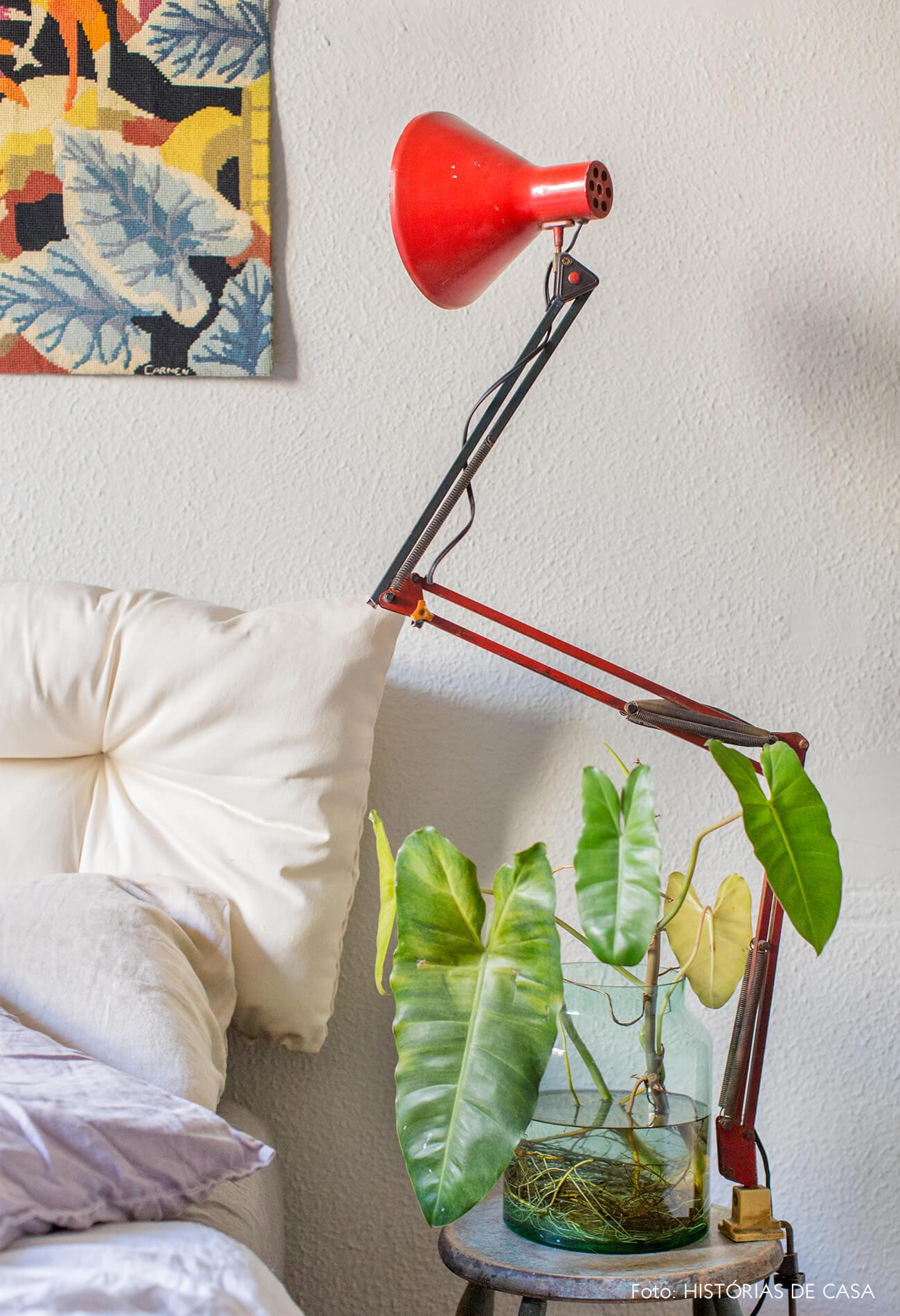 luminária vermelha e parede branca com plantas