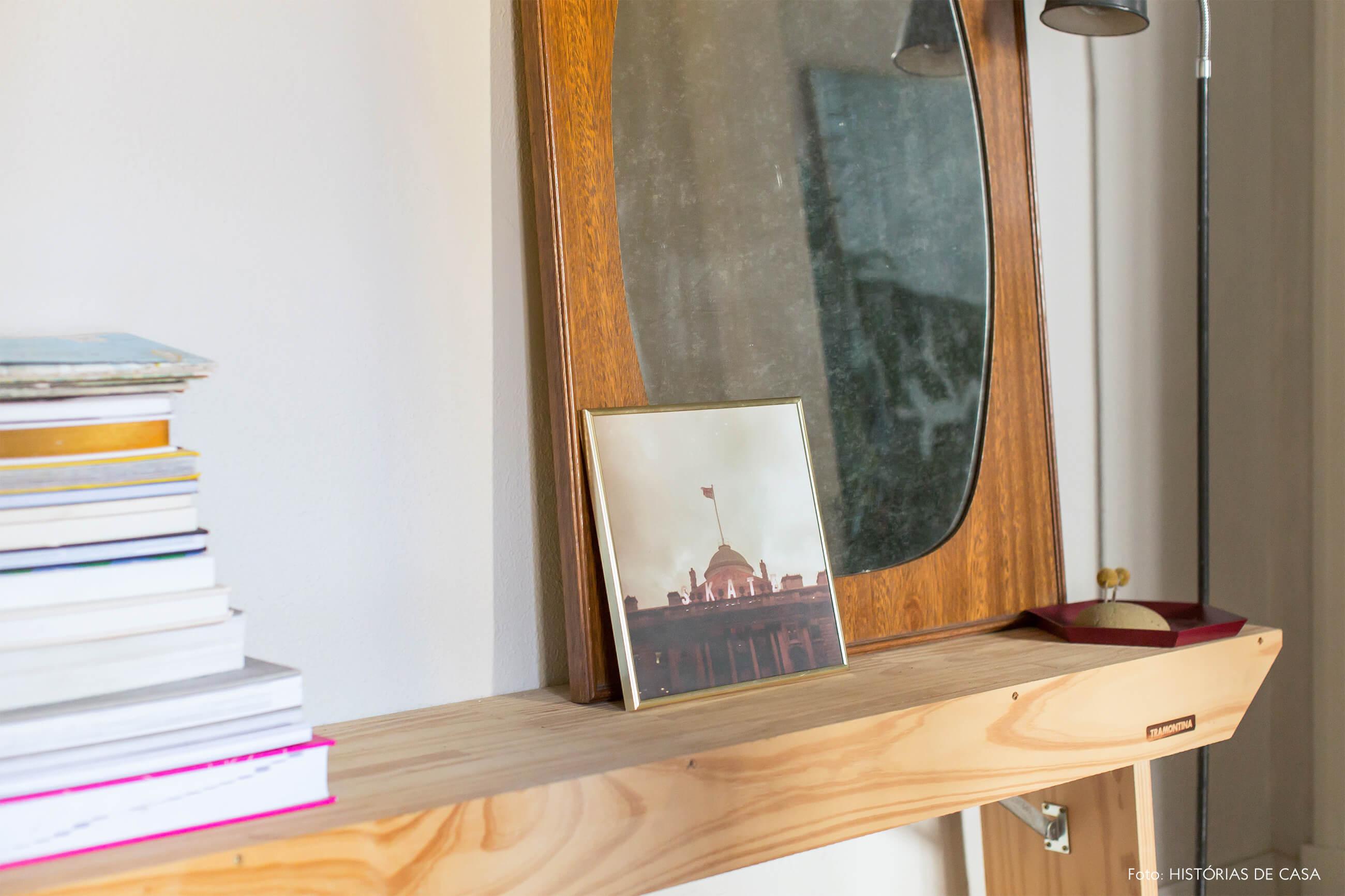 detalhe de mesa de maderia clara com parede branca e espelho