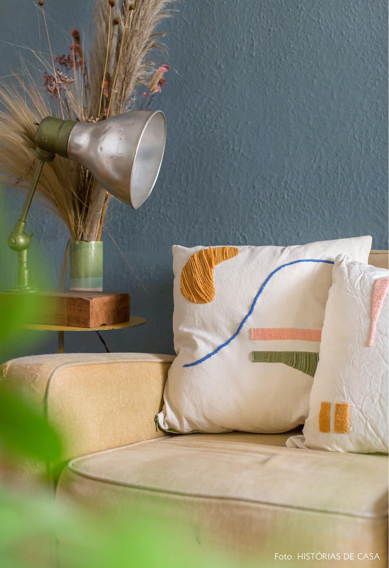 Almofada bordada em sofá bege e parede azul
