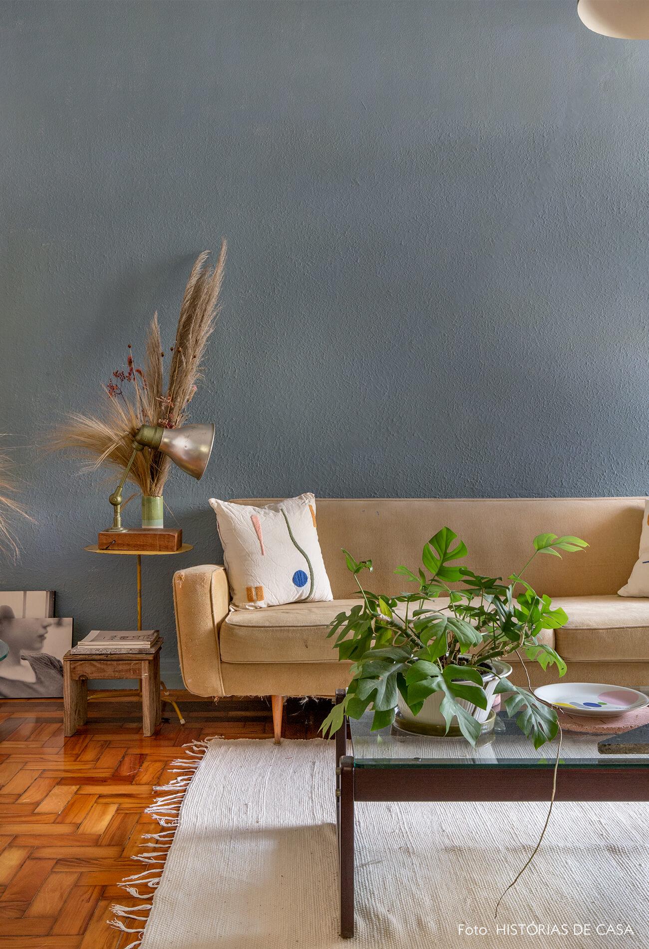 Sala com parede azul e sofá bege com tapete branco e plantas