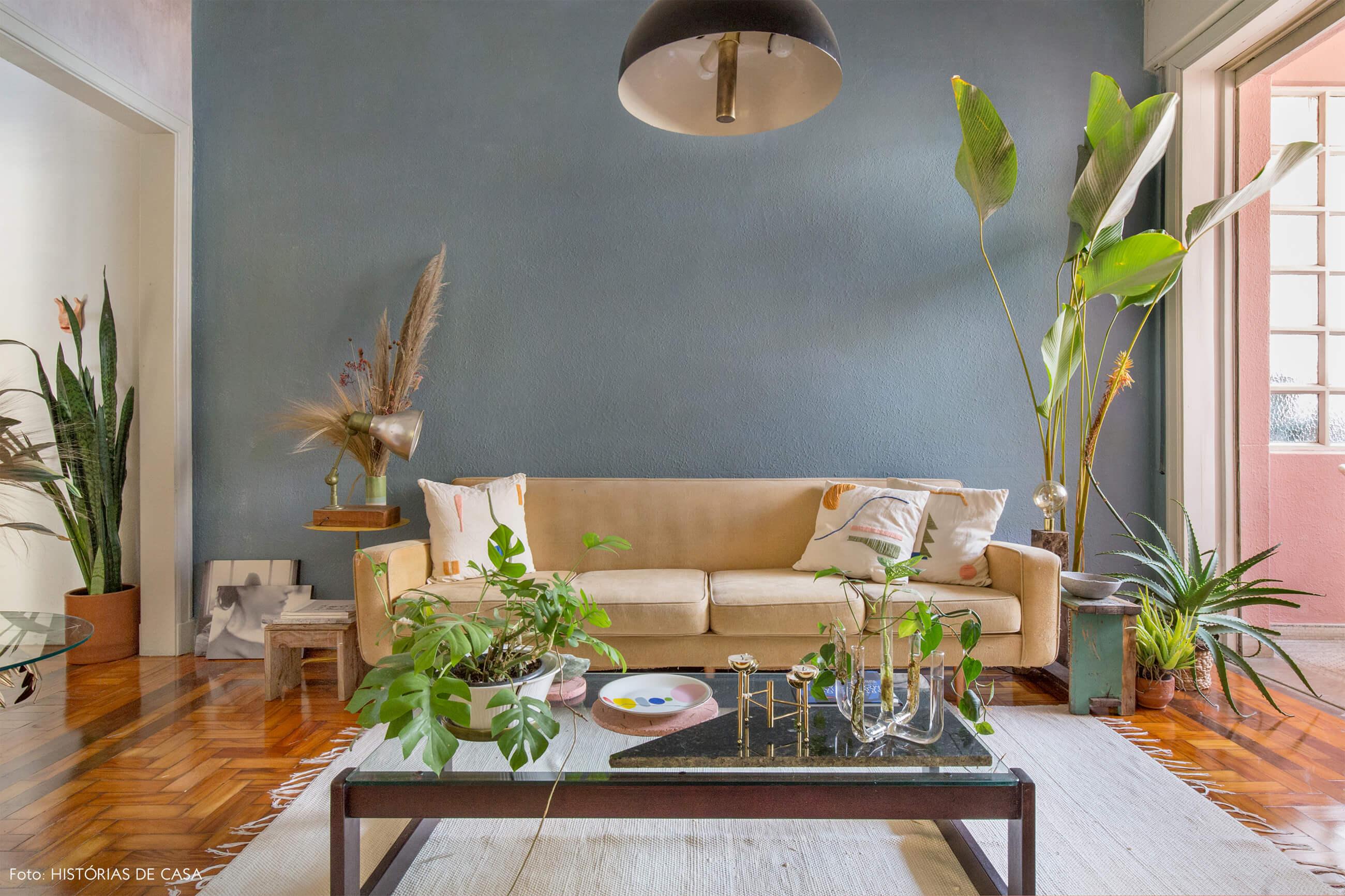 Sala com sofá bege e almofadas bordadas parede azul tapete branco e plantas