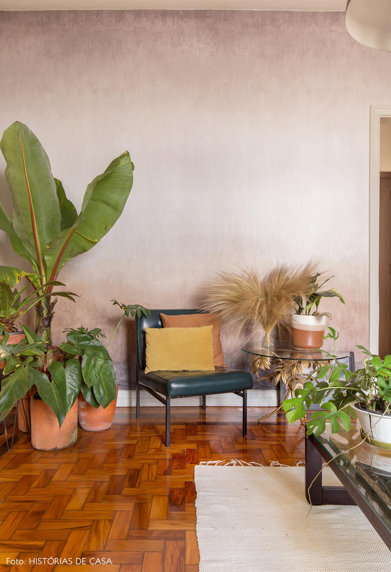 sala com parede rosa e caderia de couro com almofadas coloridas e plantas tapete branco