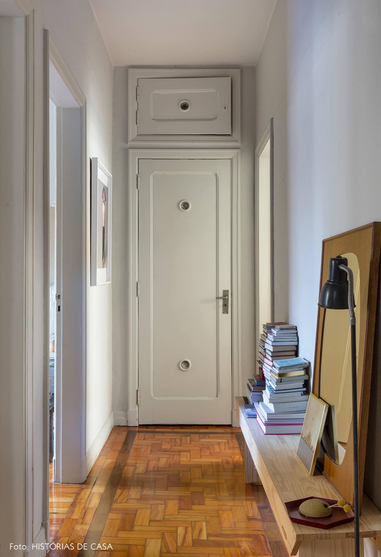 corredor com paredes brancas e piso de madeira