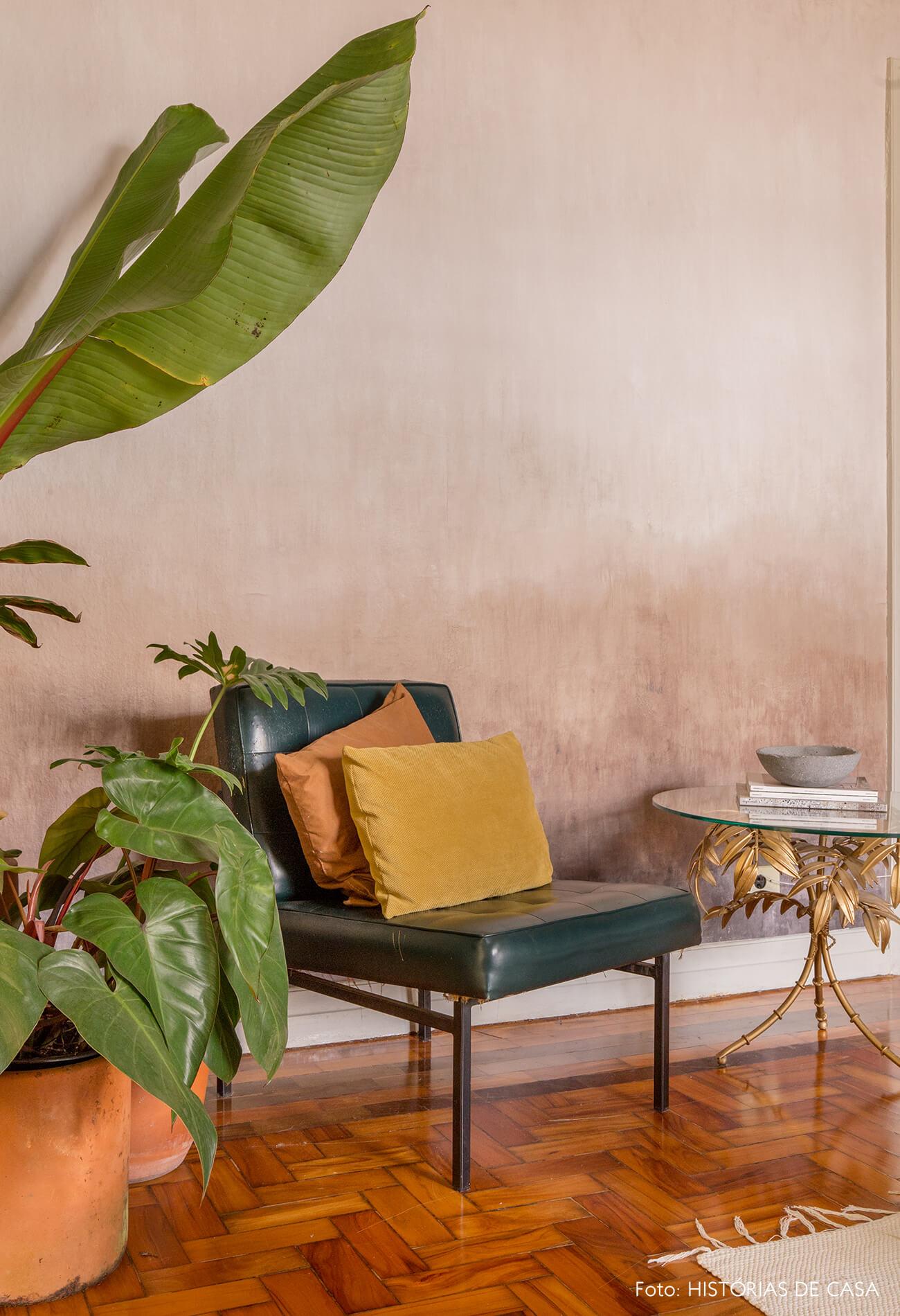 sala com parede rosa e piso de madeira cadeira de couro com almofadas coloridas e plantas