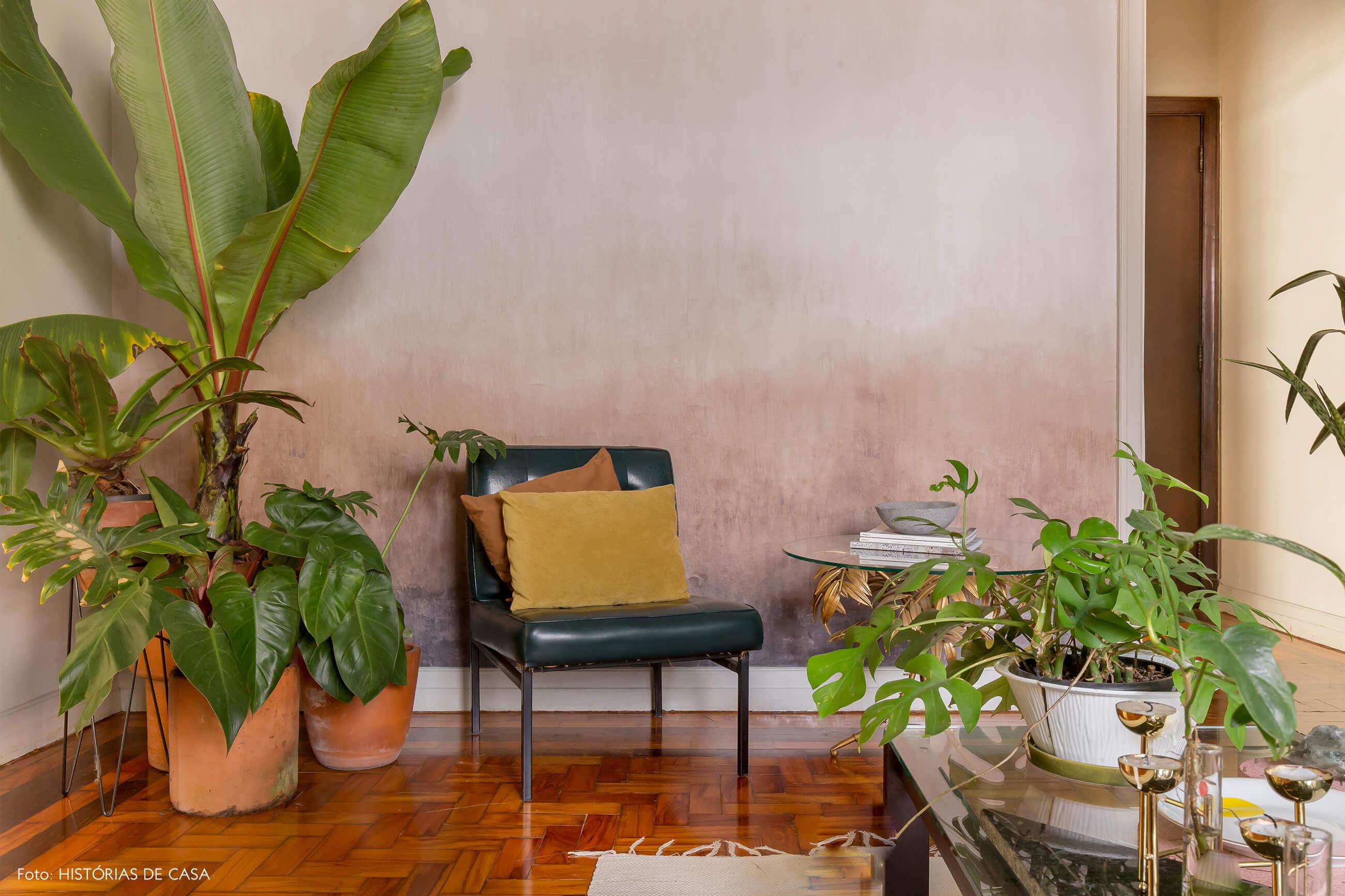 sala com parede rosa e cadeira de couro com almofadas amarela e laranja e plantas