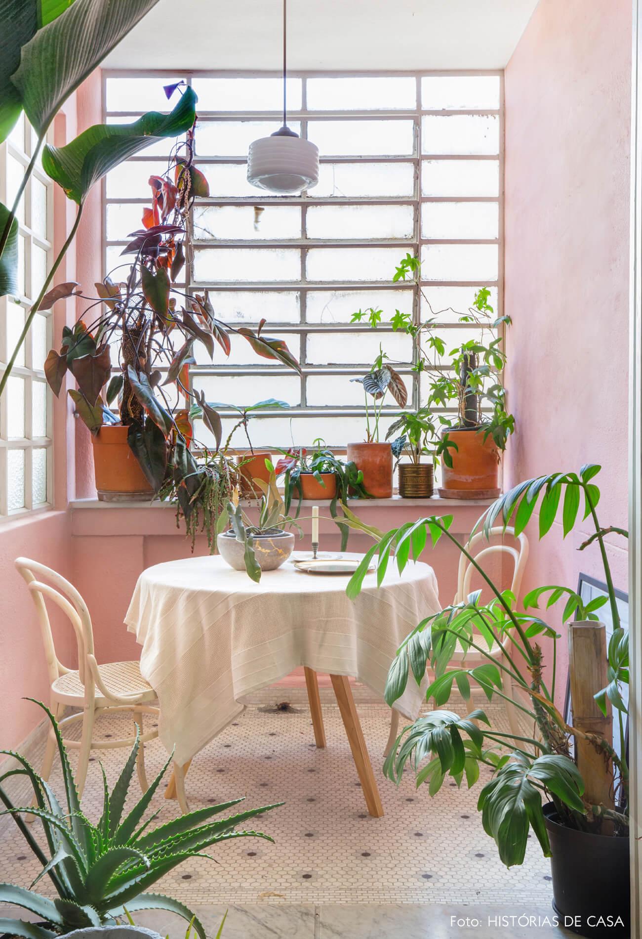parede rosa janelas plantas e mesa maderia com toalha branca