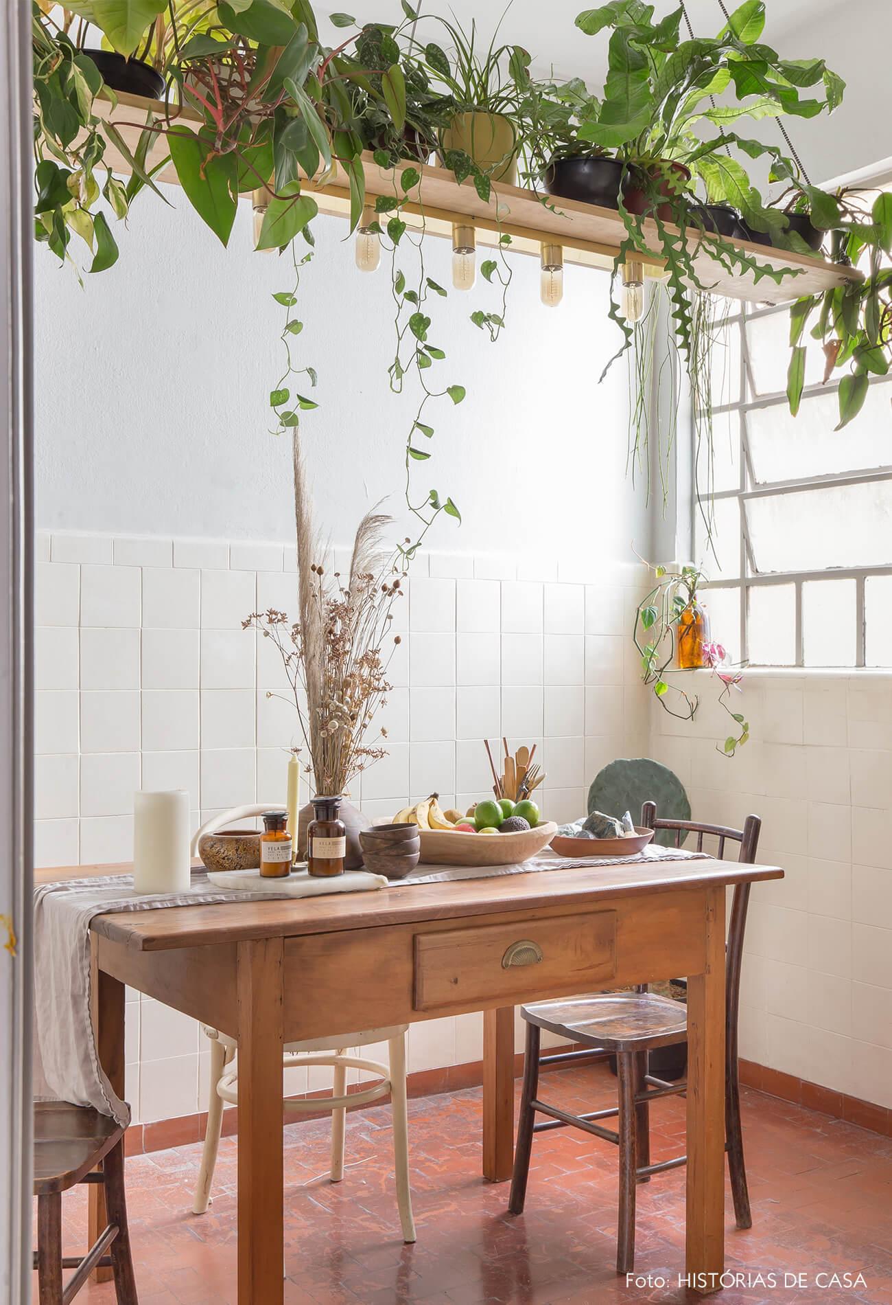 sala de jantar com móveis de madeira e paredes brancas com plantas