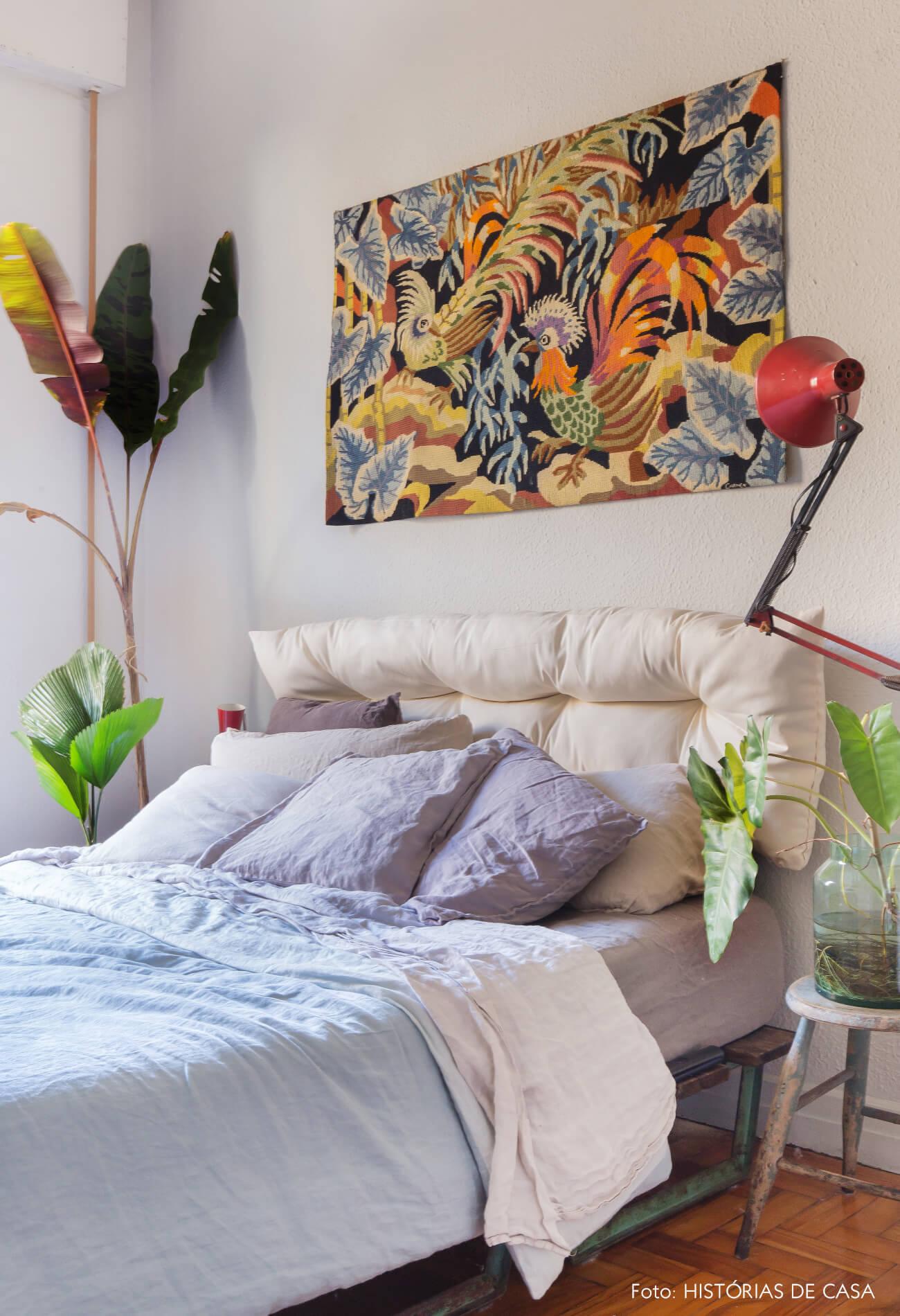 quarto cama lençol azul e quadro luminária vermelha e planta