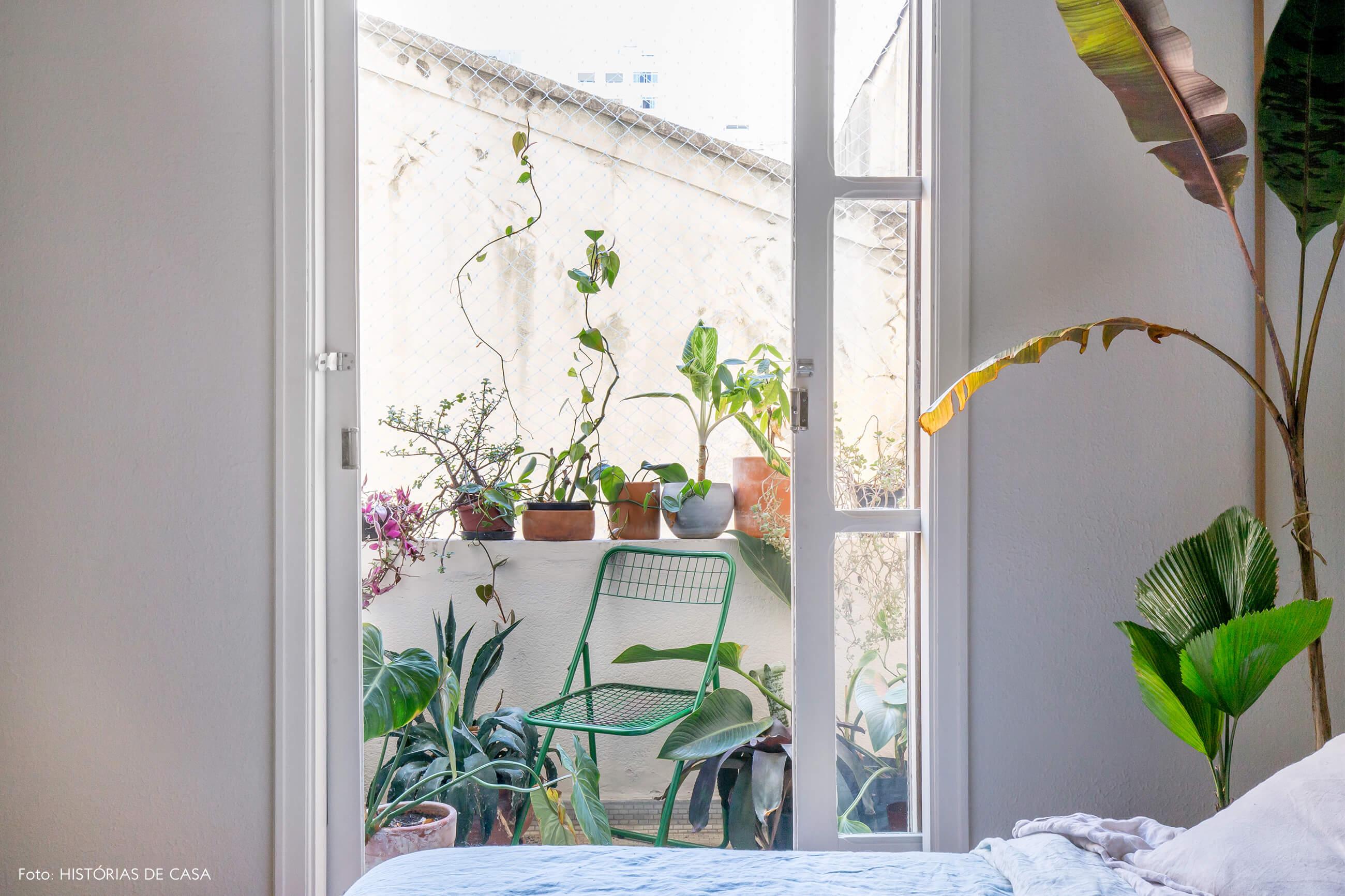 quarto com sacada e plantas paredes brancas e cadeira verde