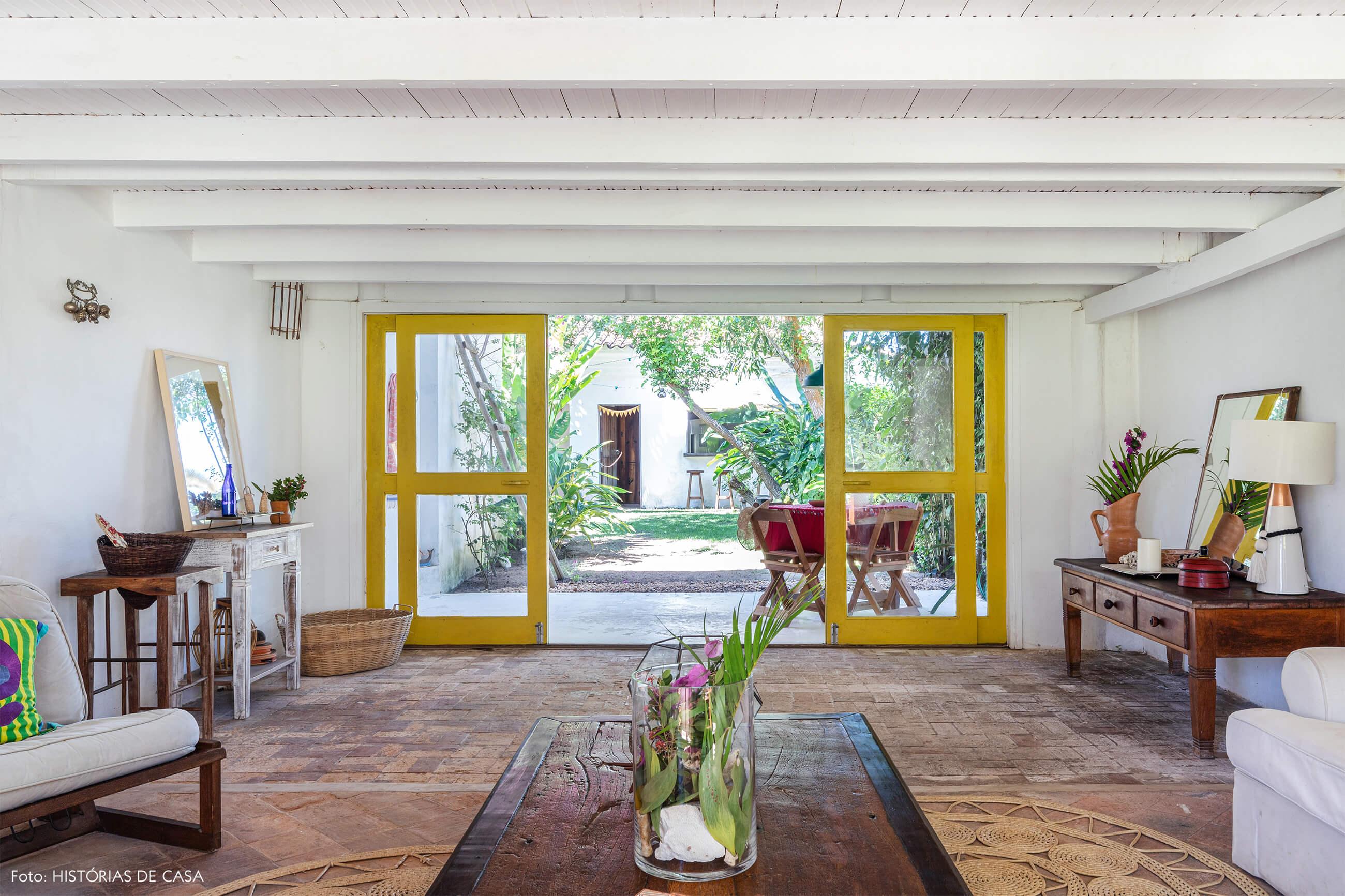 flavia-decoração-trancoso-sala-com-itens-de-madeira-e-varanda-com-pora-amarela