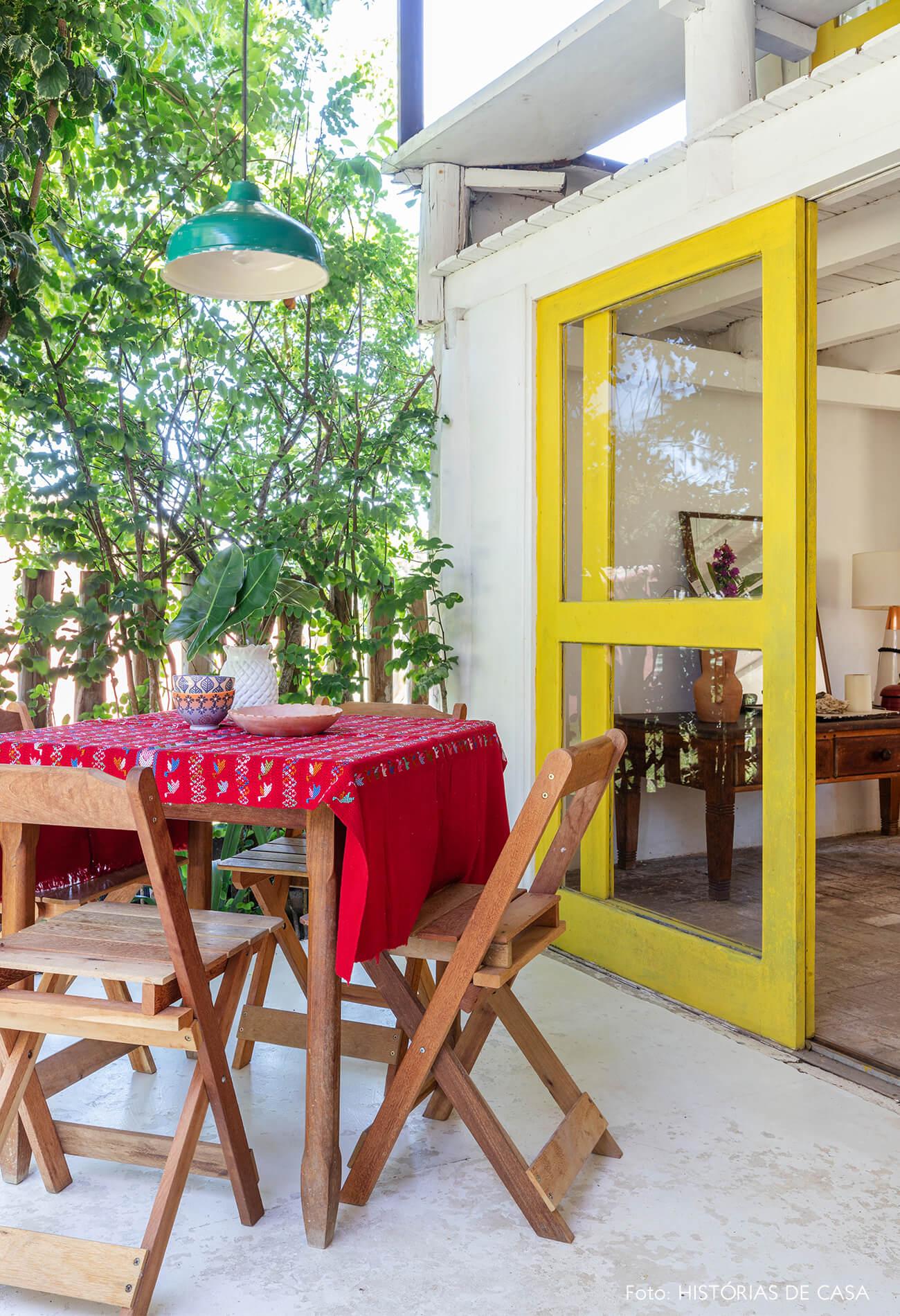 flavia-decoração-trancoso-varanda-com-mesa-de-madeira-e-porta-amarela