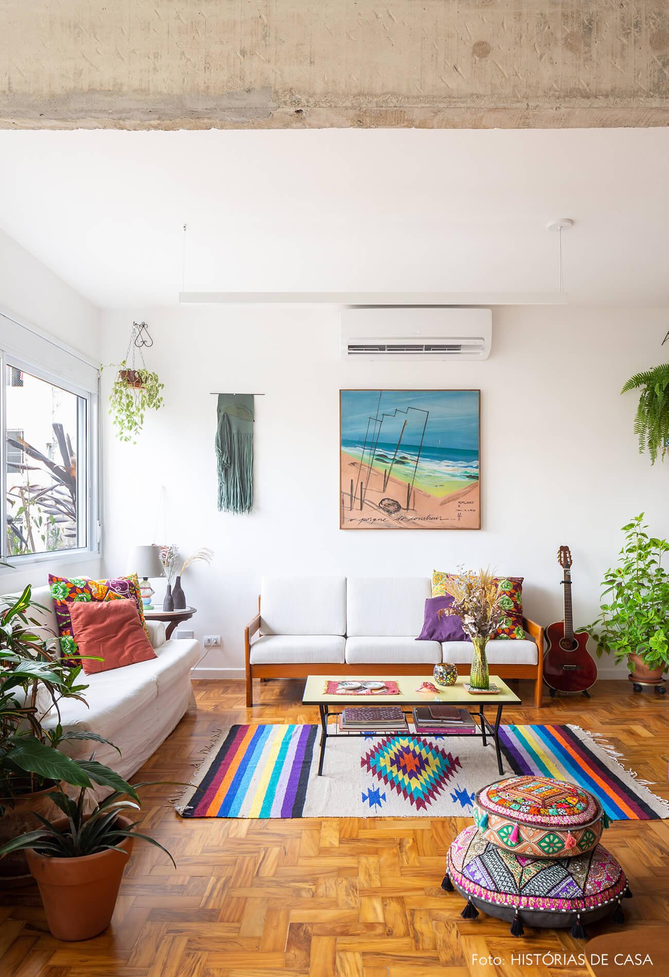 decoração sala com sofás neutros e objetos coloridos