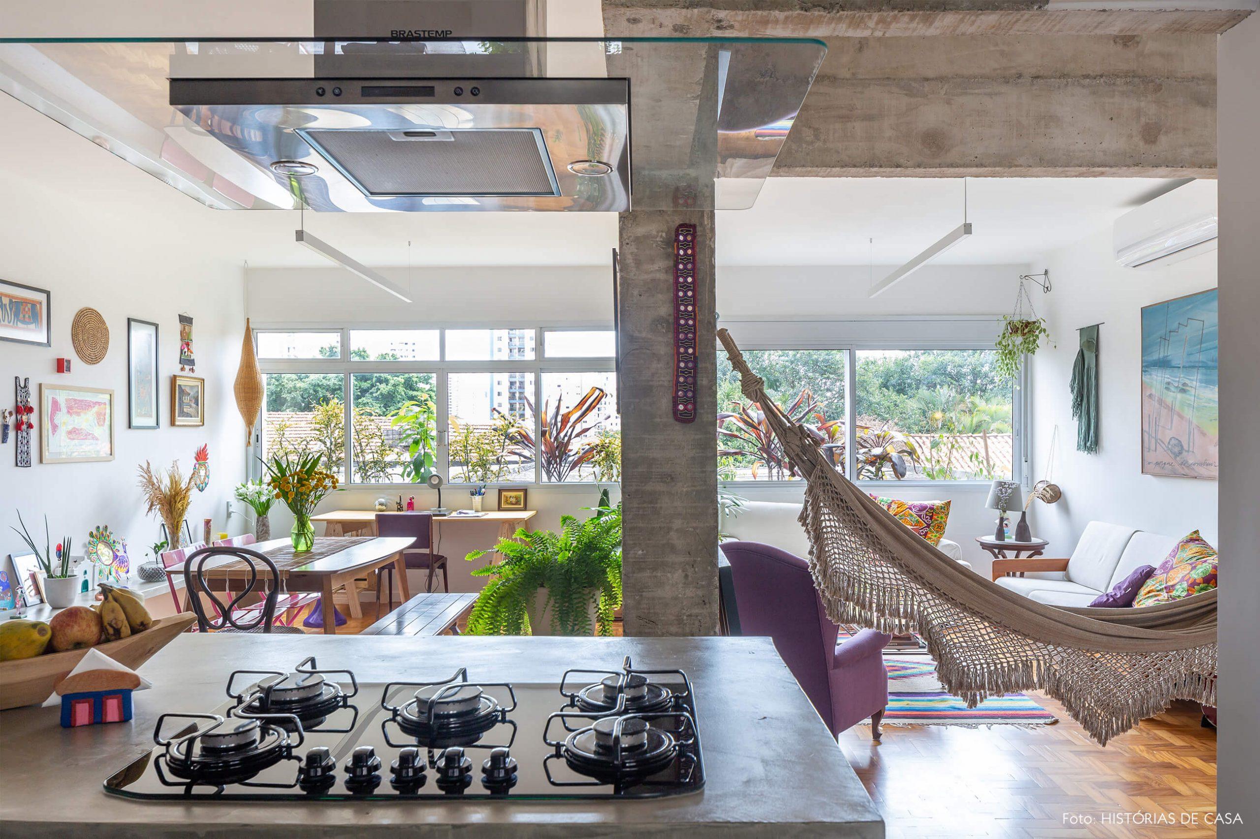 decoração cozinha com bancada de concreto e sala com chão de taco e rede