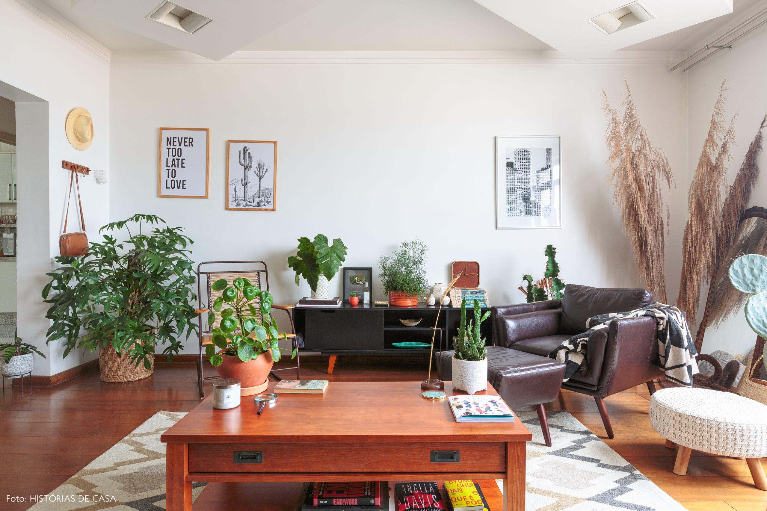 decoração sala com poltrona de couro mesa de madeira e pufe branco