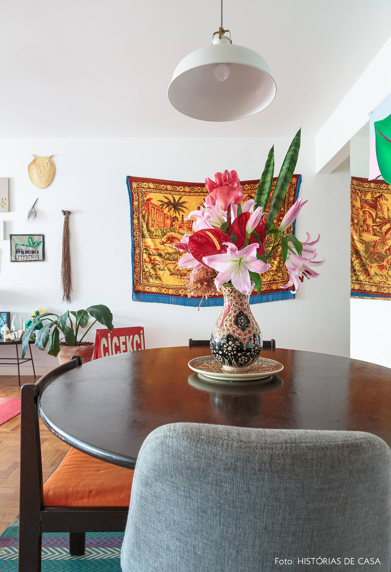 decoração sala jantar com tapeçaria na parede e mesa de madeira escura