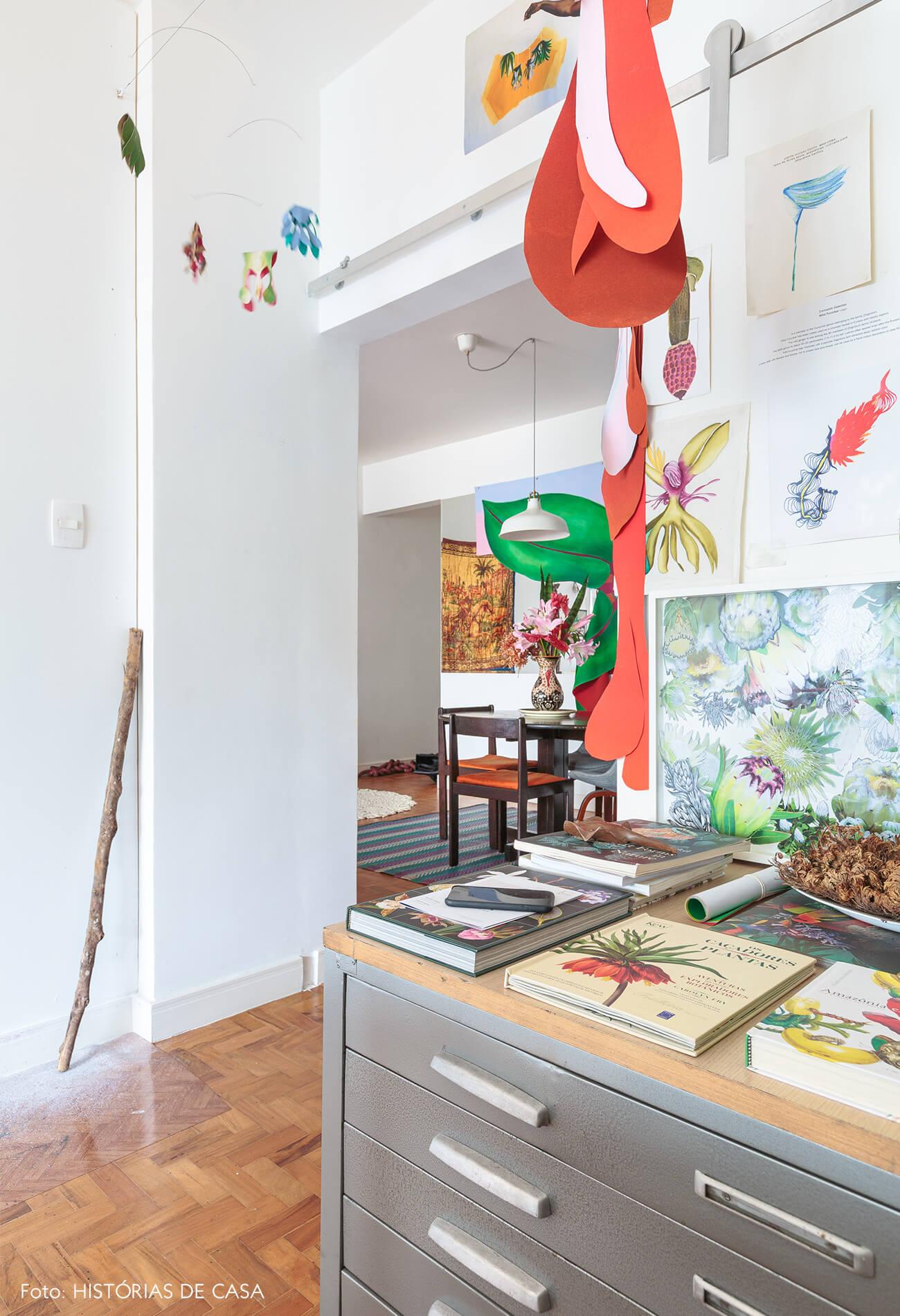 decoração atelie com obras de arte e mobile de flores