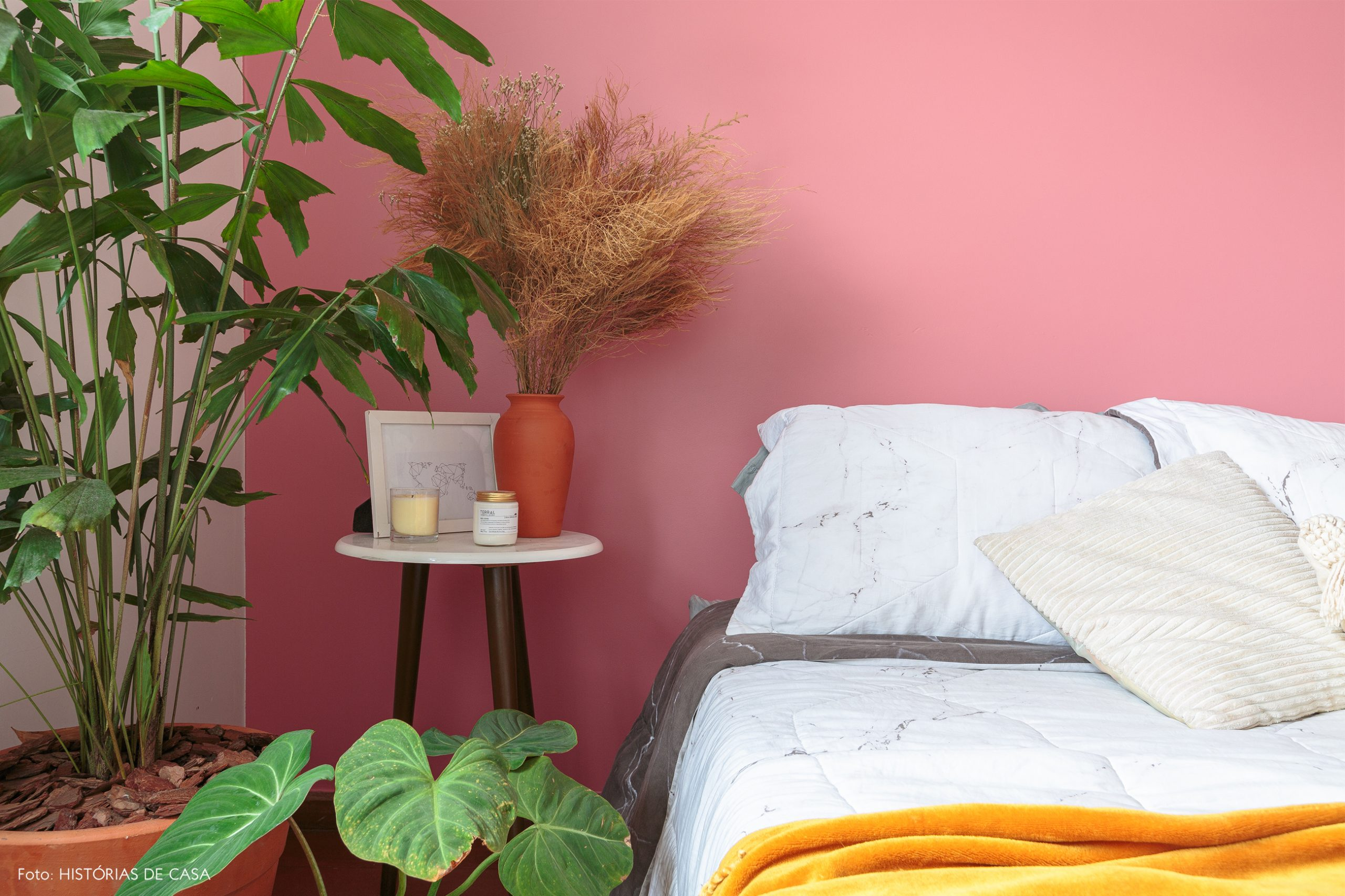 decoração quarto com parede rosa plantas e mesa branca
