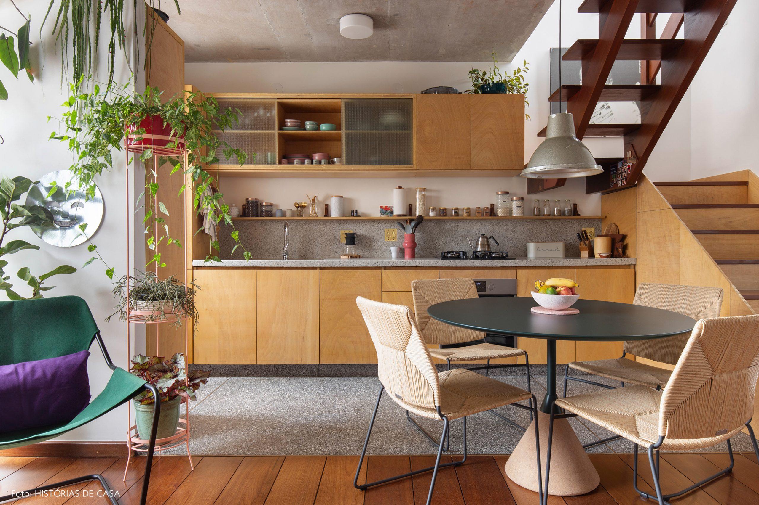 decoração cozinha com armarios de madeira clara e mesa redonda escura
