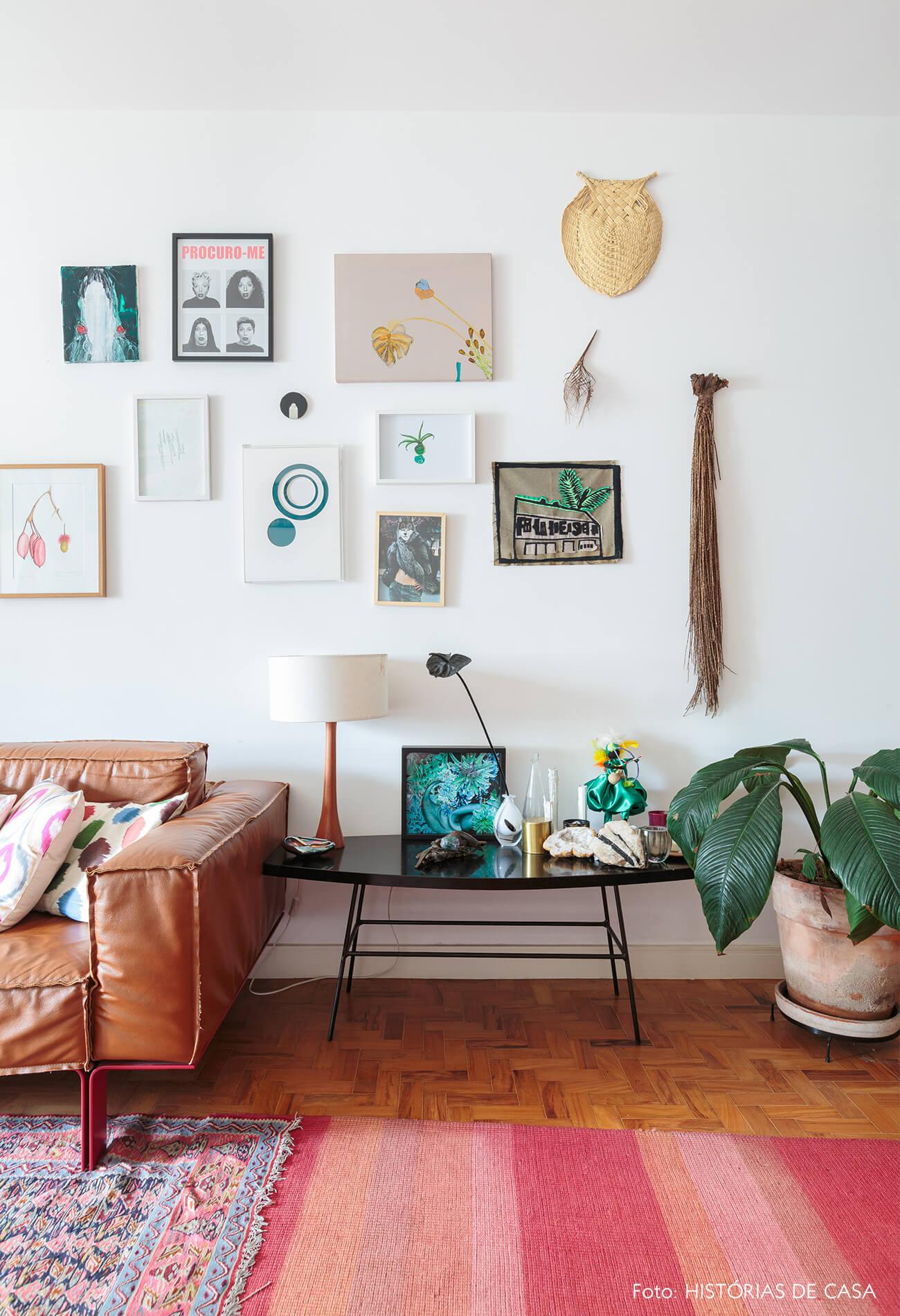 decoração sala com vários quadros e mesa lateral preta