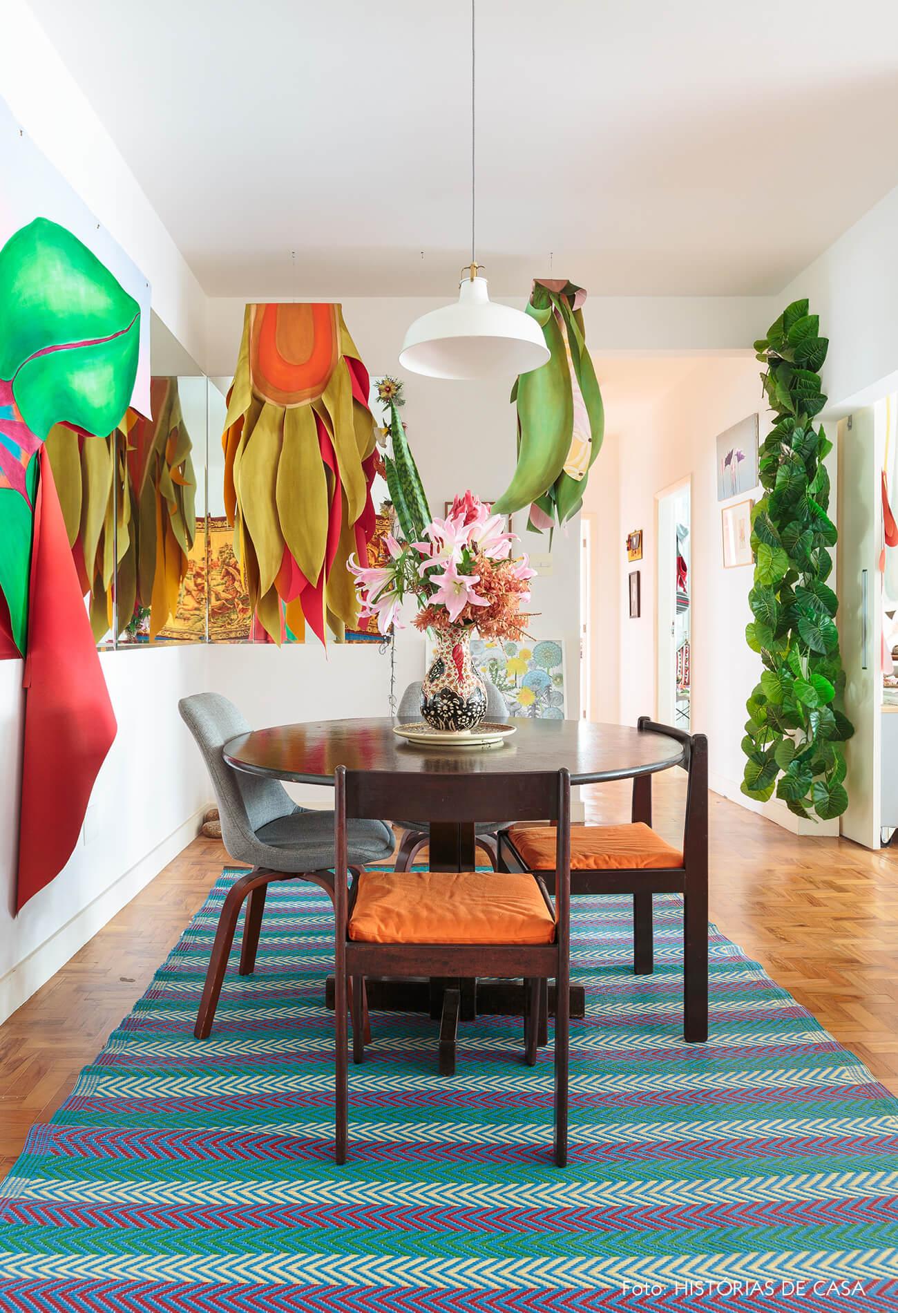 decoração sala jantar colorido com obras de arte na parede e mesa de madeira