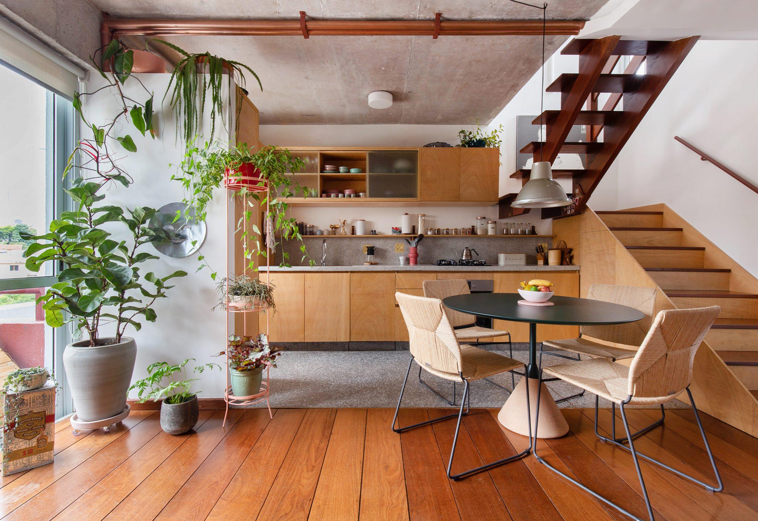 decoração cozinha com armarios e escada de madeira clara e mesa redonda escura