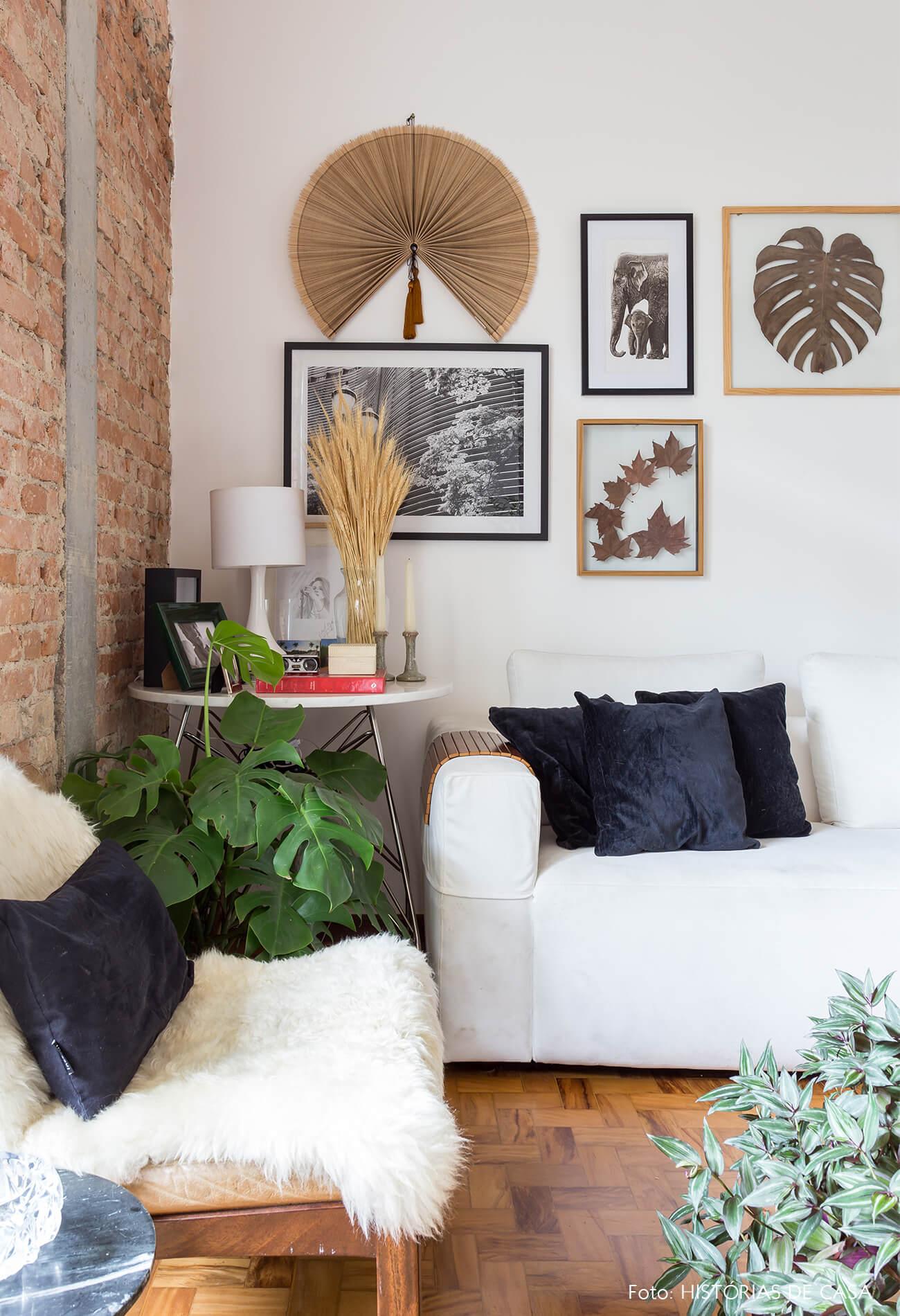 decoração sala com parede de tijolos quadros e sofá branco