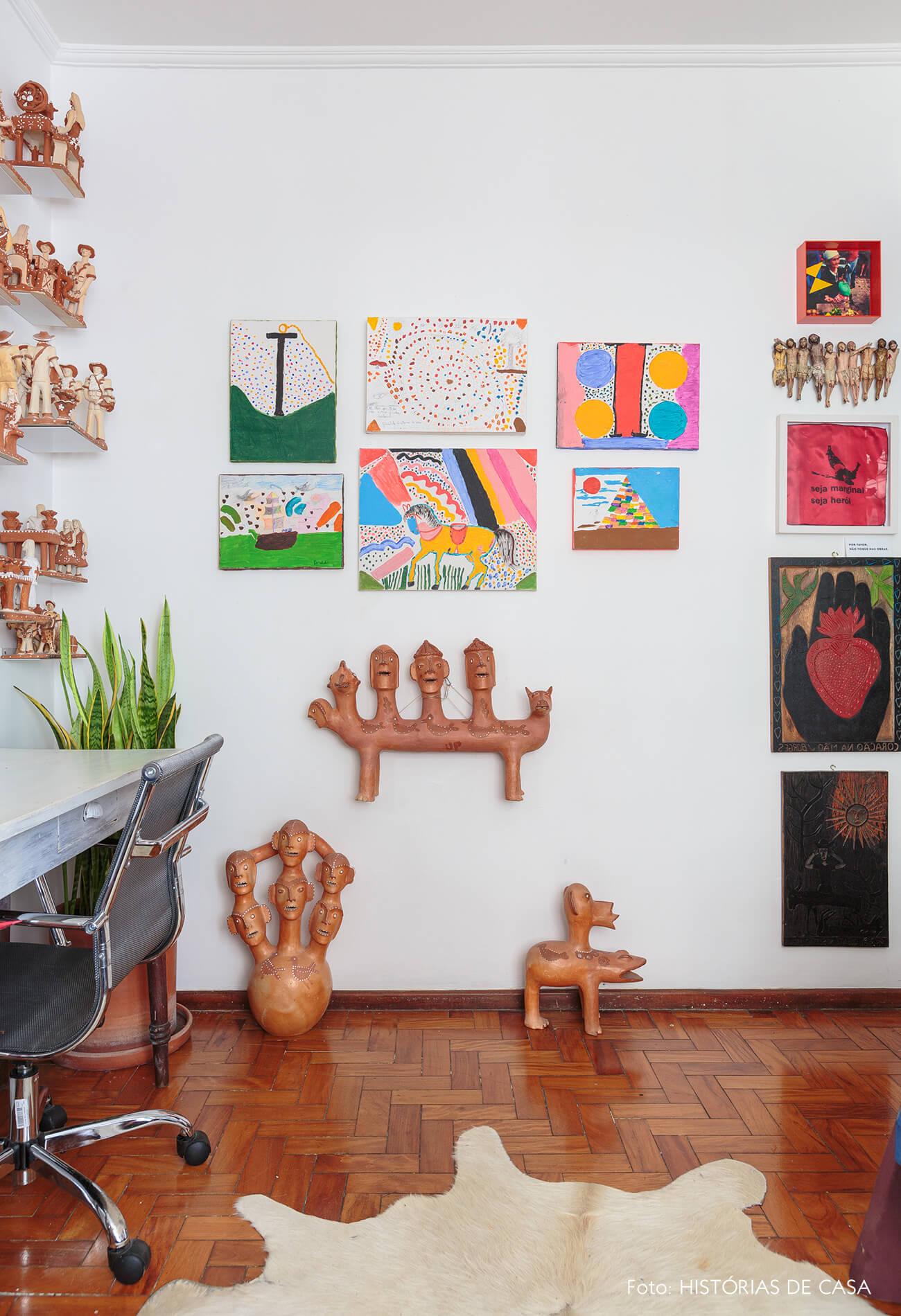 decoração home office com muitos quadros e ceramicas