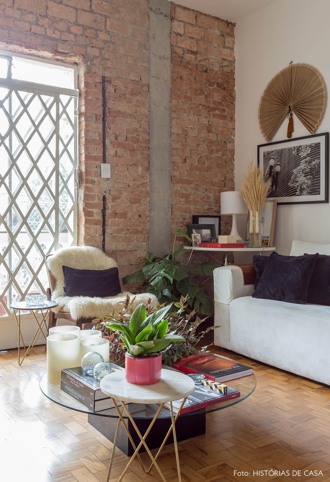 decoração sala com parede de tijolos mesas com pés dourados e sofá branco