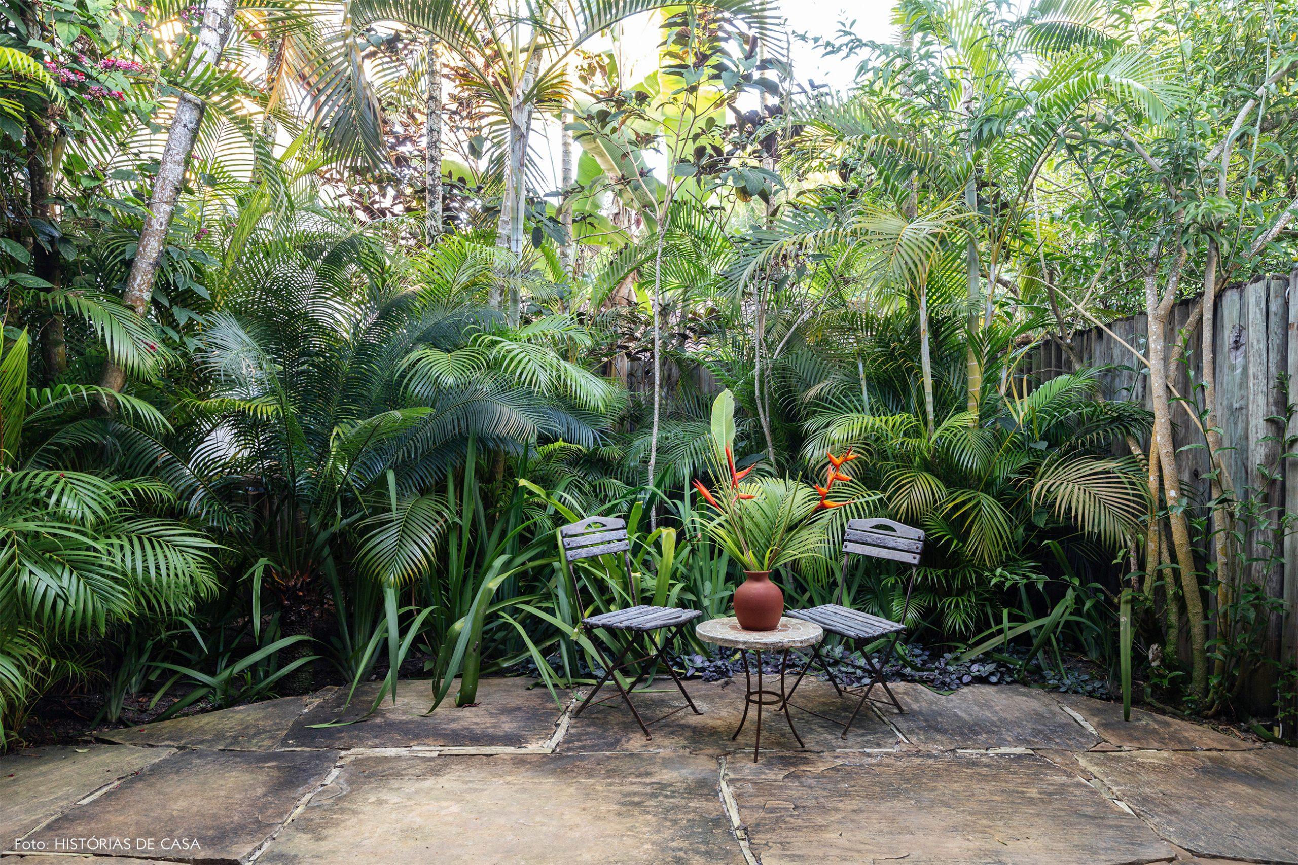 decoração Trancoso jardim com muitas plantas e mesa e cadeira de metal