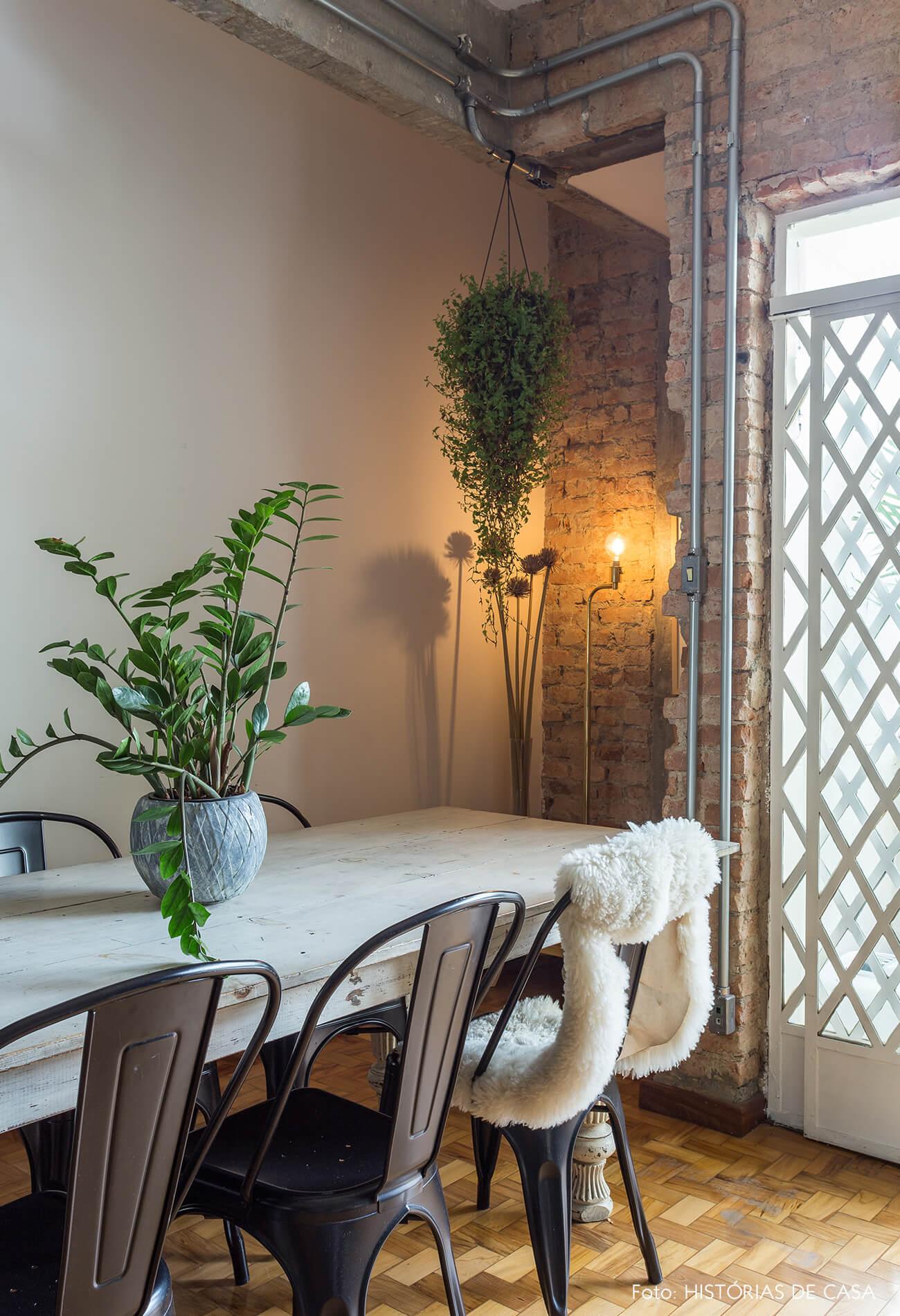 decoração sala com parede de tijolos e mesa grande de madeira