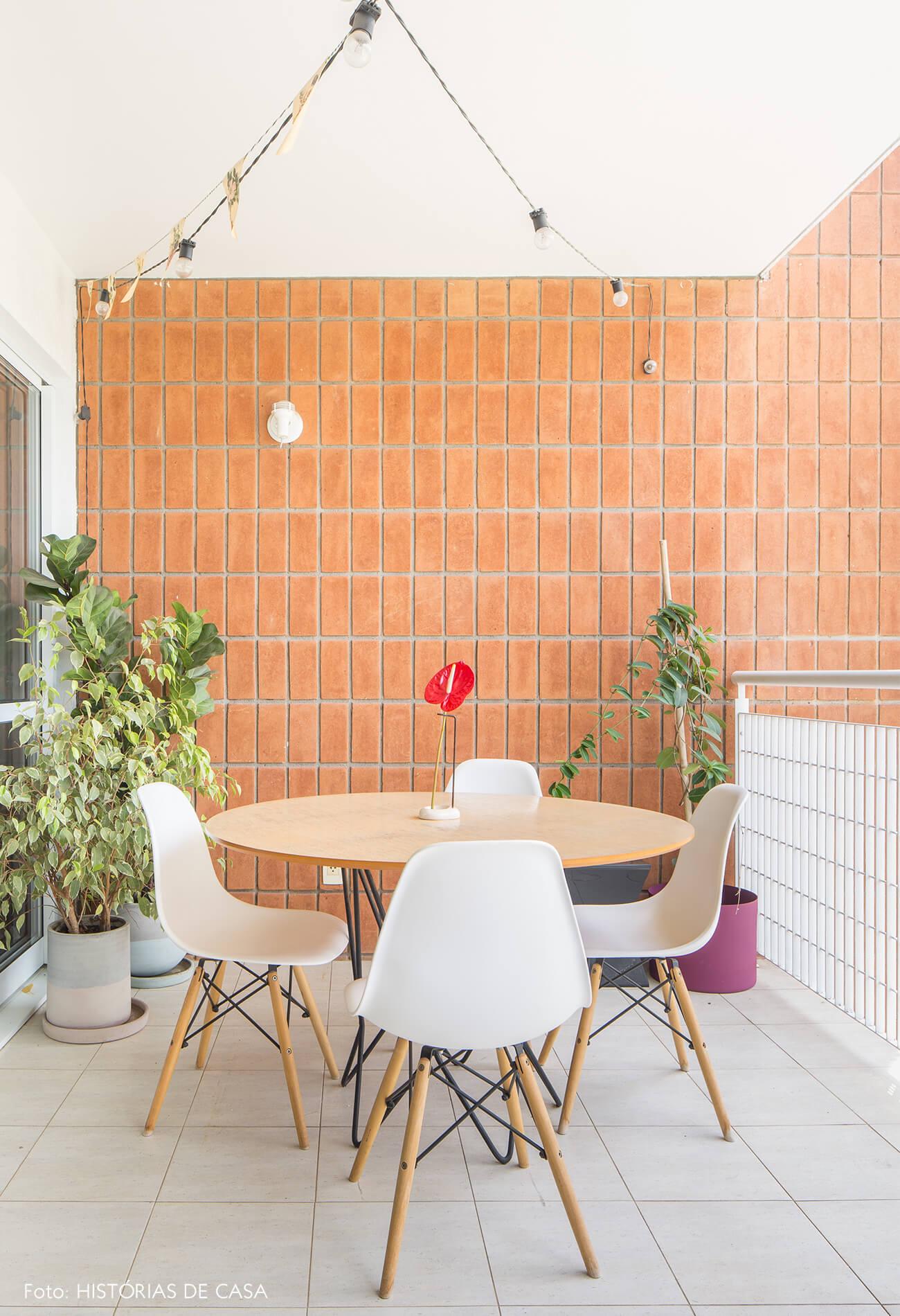 decoração varanda com parede de tijolo e cadeira eames
