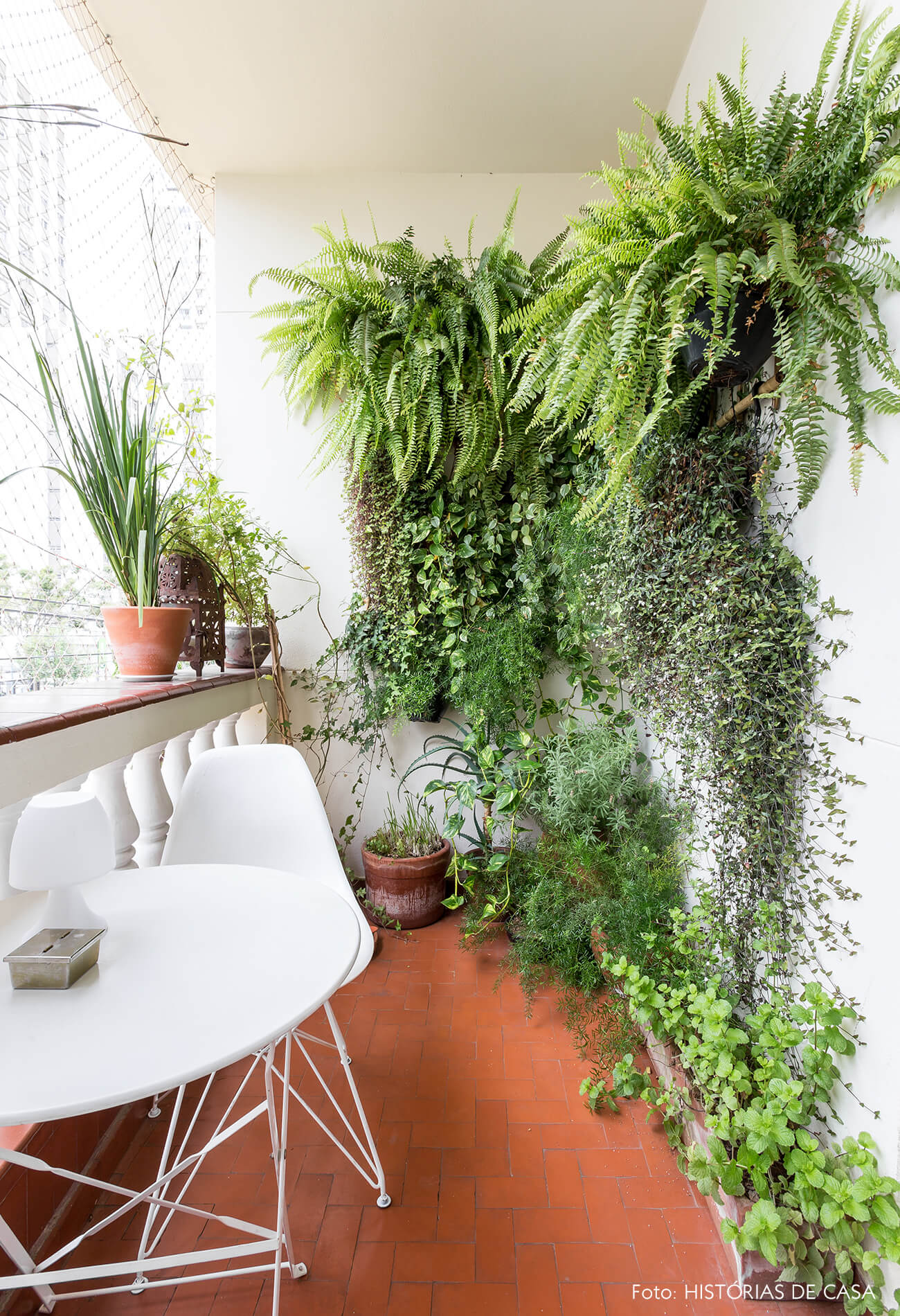 decoração varanda com muitas plantas e mesa e cadeira brancas
