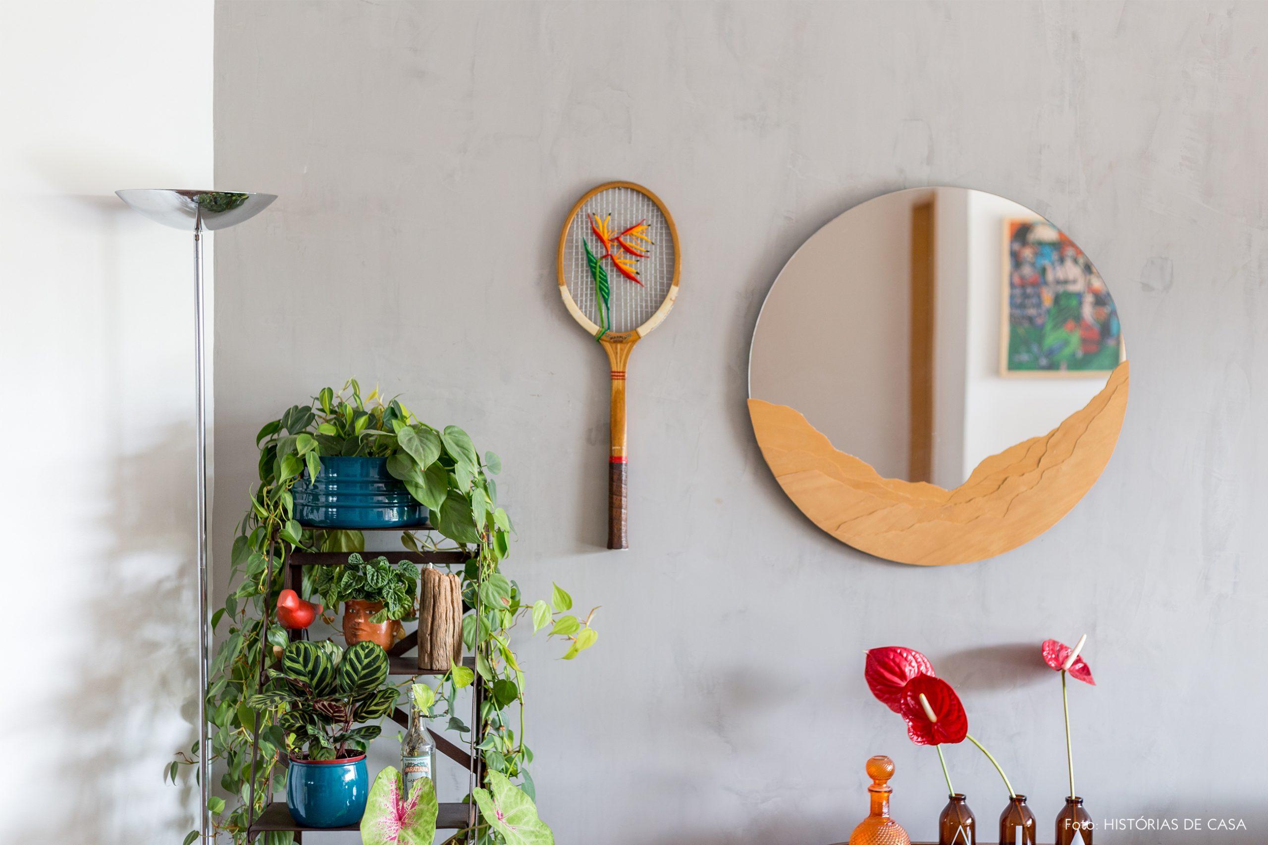 decoração sala com parede cinza espelho redondo e estante com muitas plantas