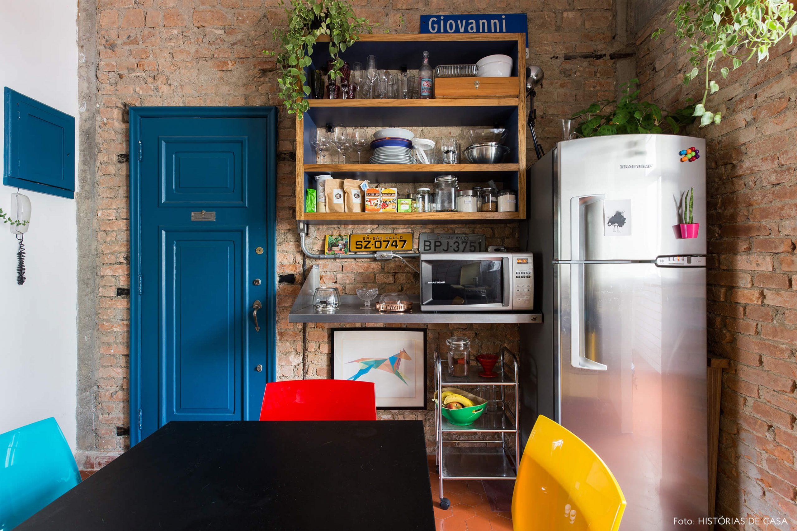 decoração cozinha com parede de tijolos e porta azul