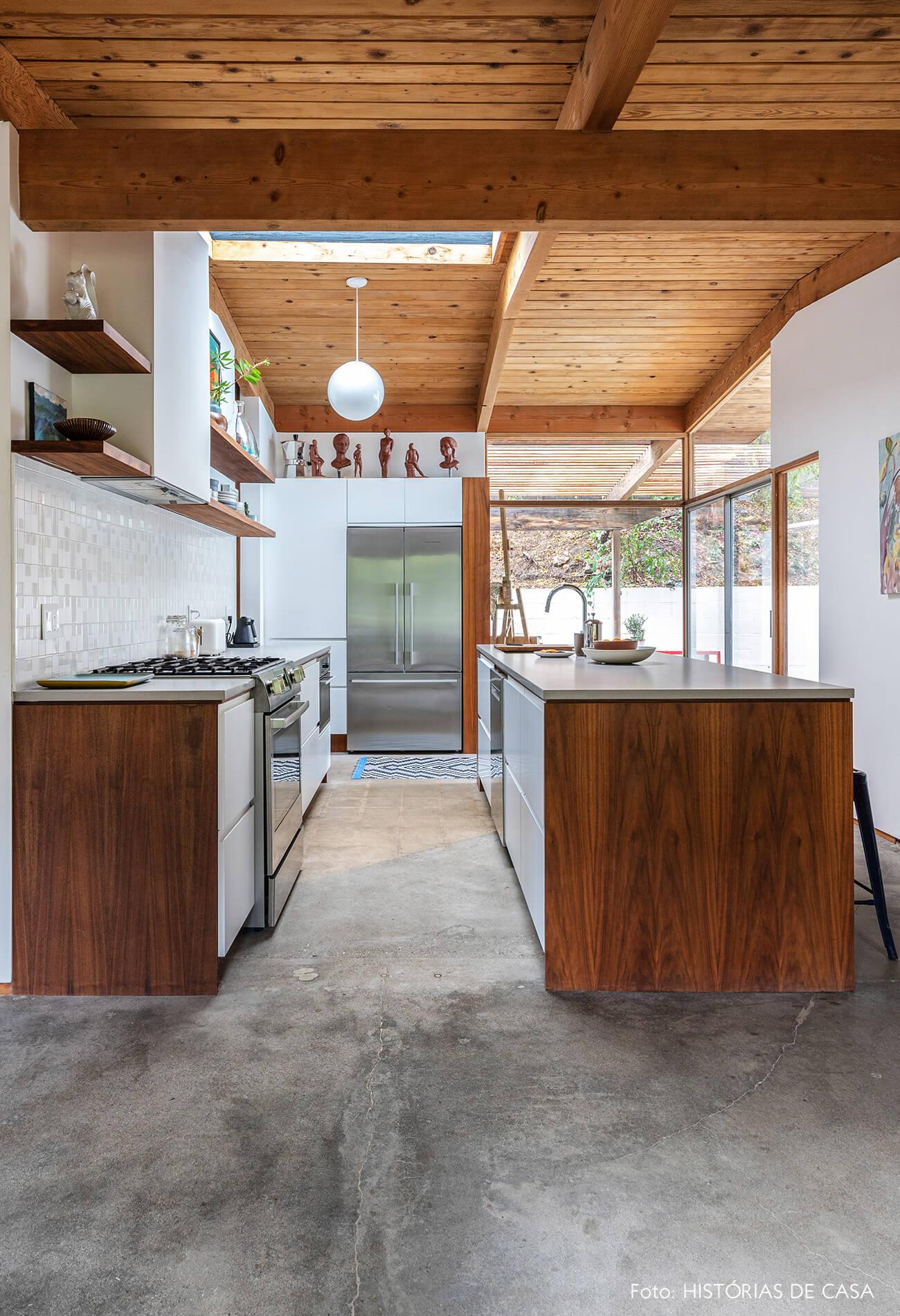 decoração casa de vidro e madeira cozinha com armarios e bancada de madeira e chao cimento