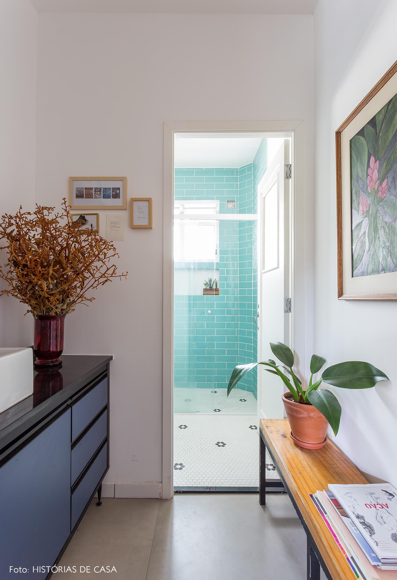 decoração banheiro com banco de madeira e azulejos azuis