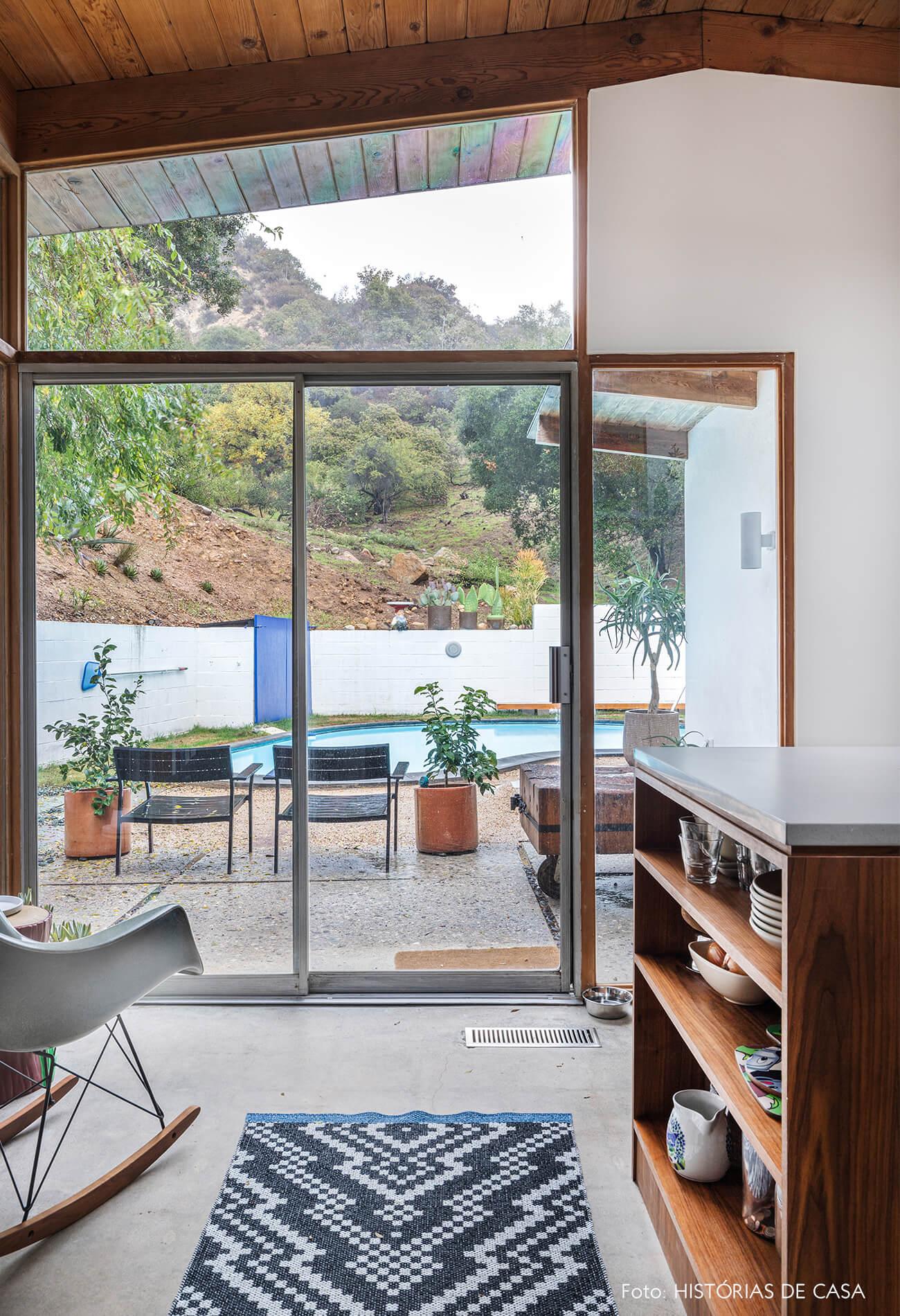 decoração casa de vidro e madeira caderia eames com vista pra piscina