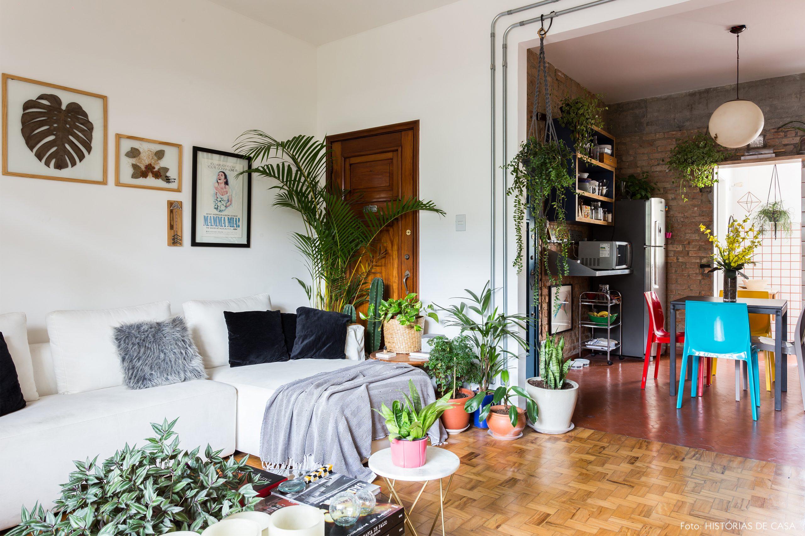 decoração sala com muitas plantas cesto de palha e sofá branco
