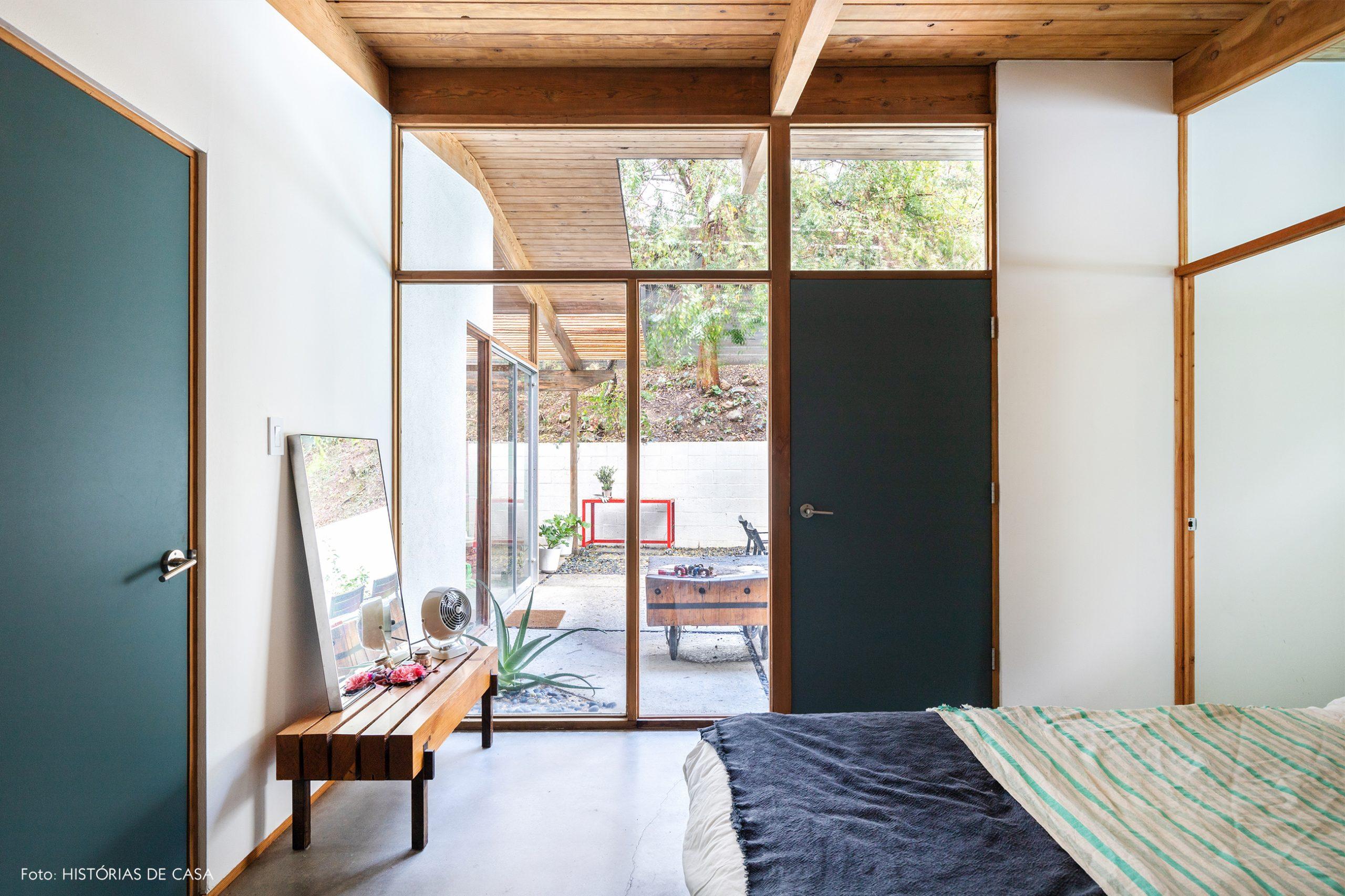 decoração casa quarto com paredes de vidro portas azuis e banco de madeira