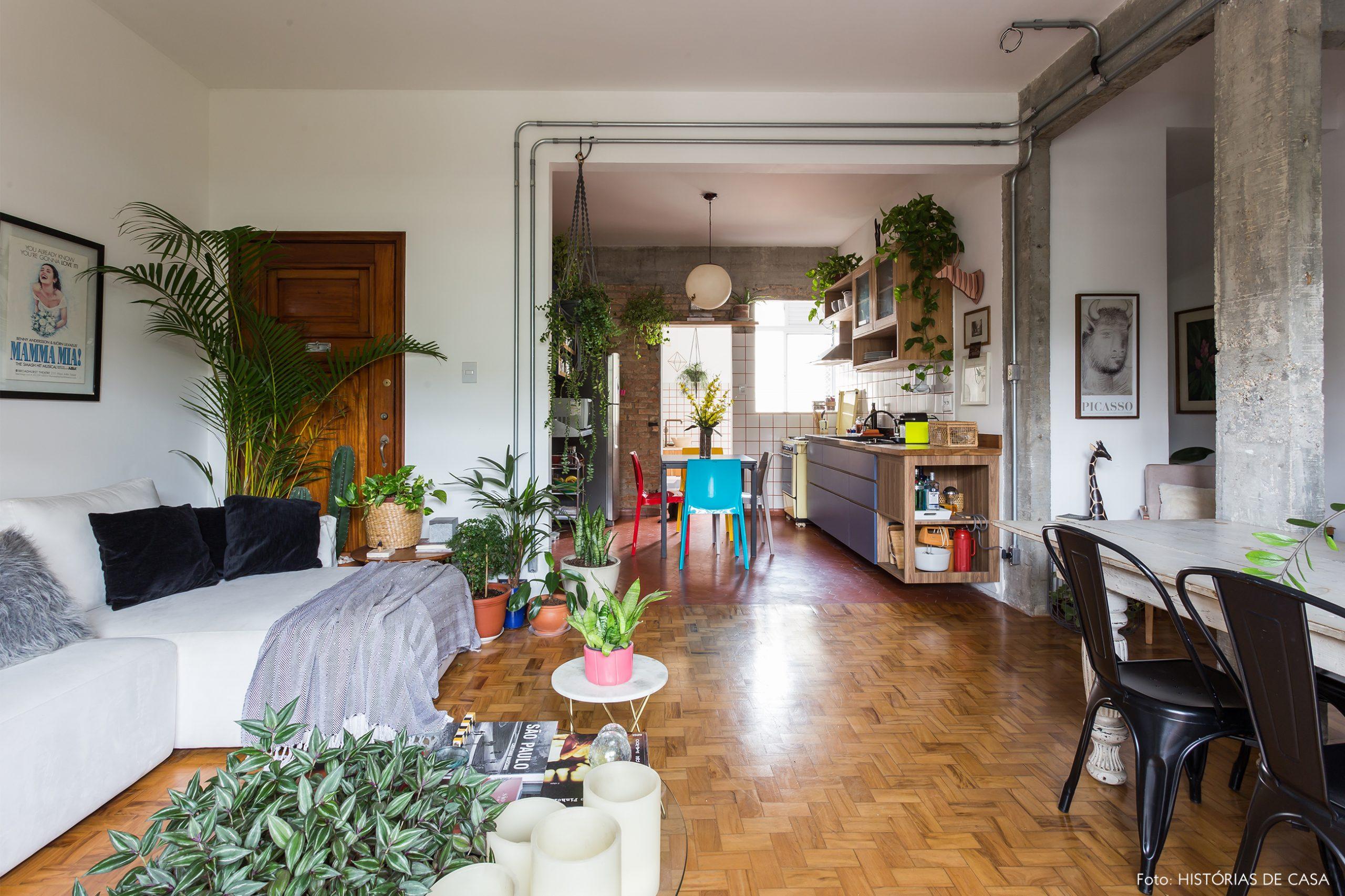 decoração sala com muitas plantas sofá branco e chão de taco