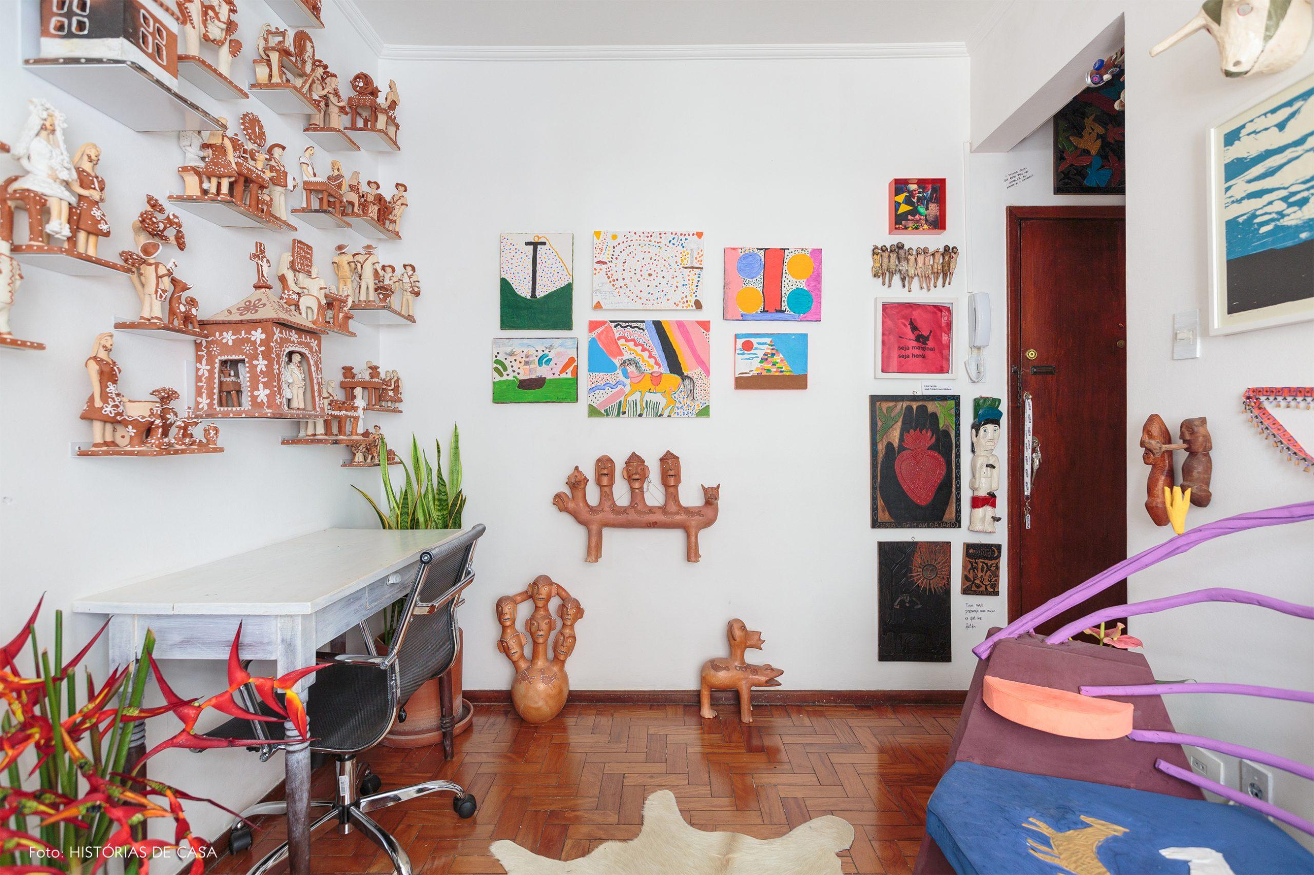 decoração home office colorido com muitos quadros e ceramica