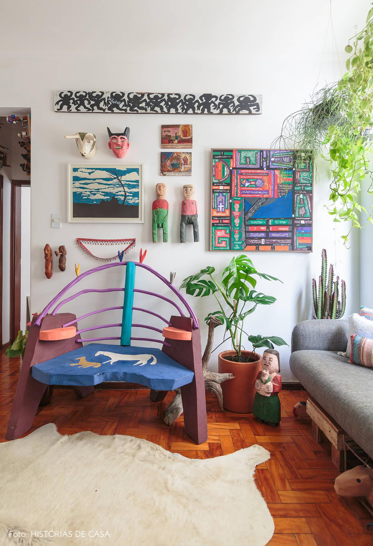 decoração sala colorida com muitos quadros e poltrona de madeira