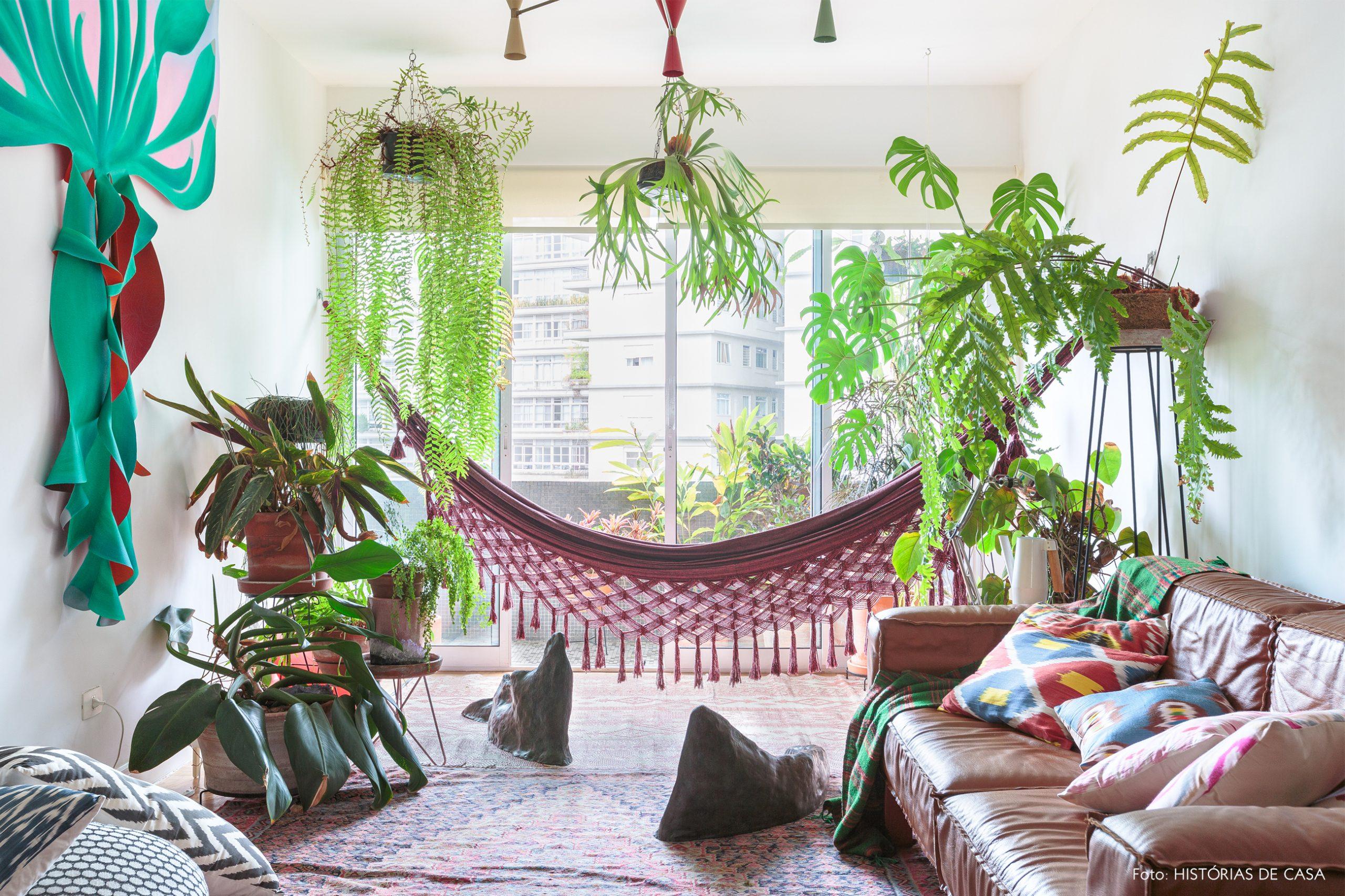 decoração sala com muitas plantas e rede vermelha