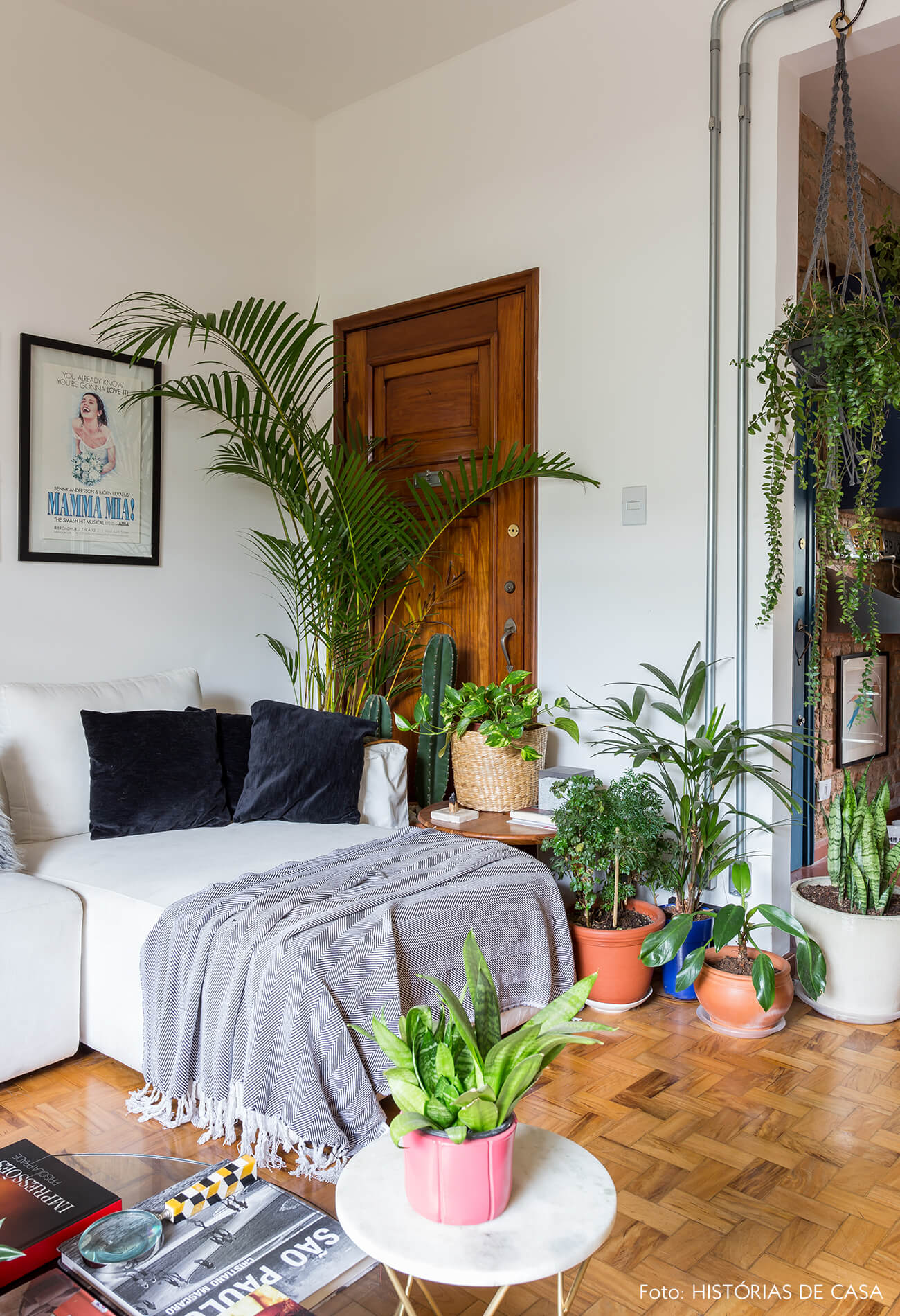 decoração sala com muitas plantas cesto e sofá branco